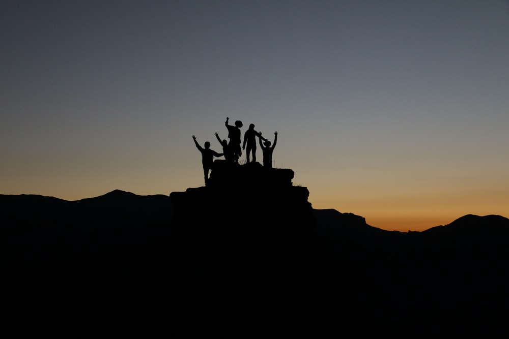 Silhouette of a group of friends with arms raised atop a mountain peak during sunset