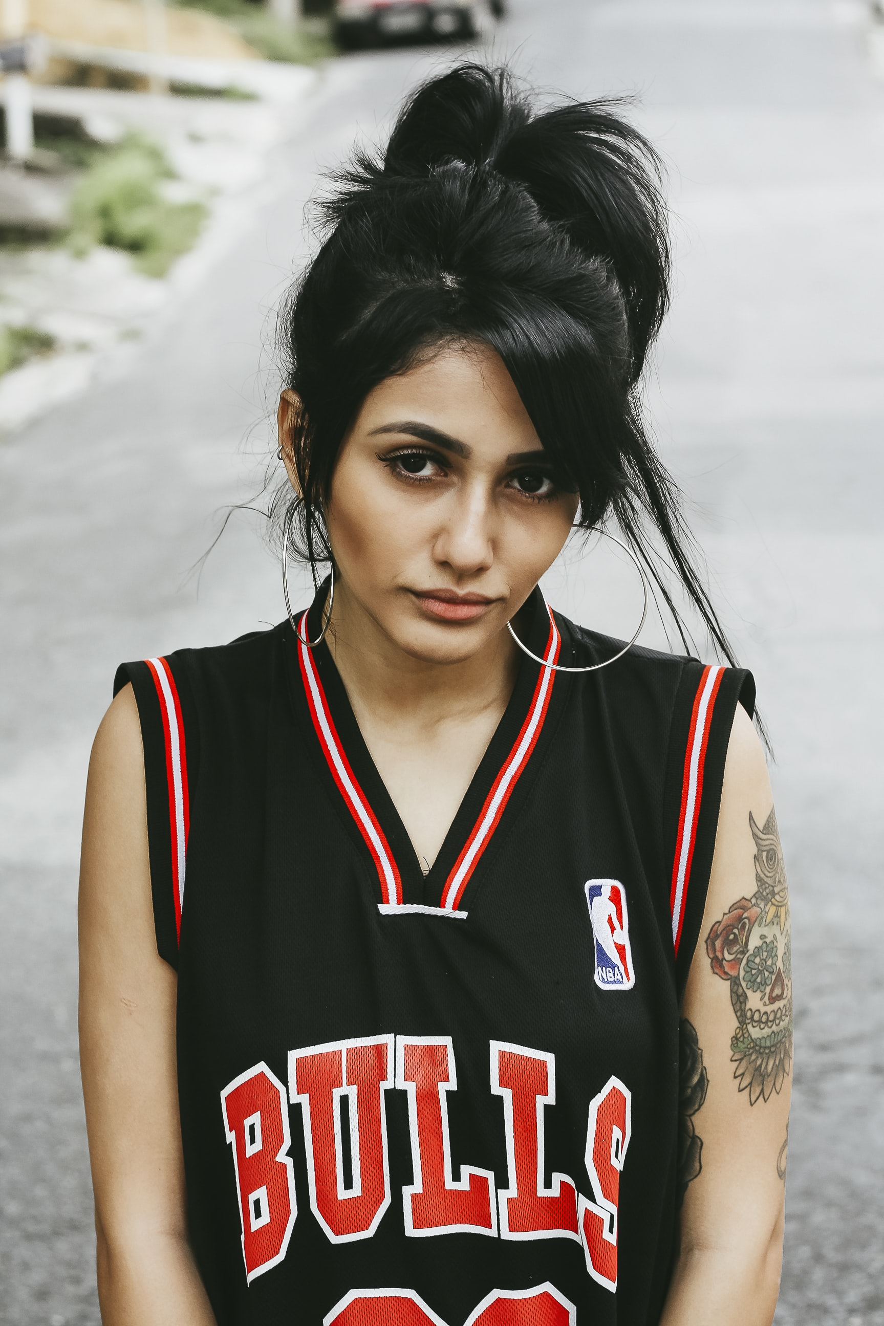 Woman in a retro Bulls basketball jersey and hoop earrings