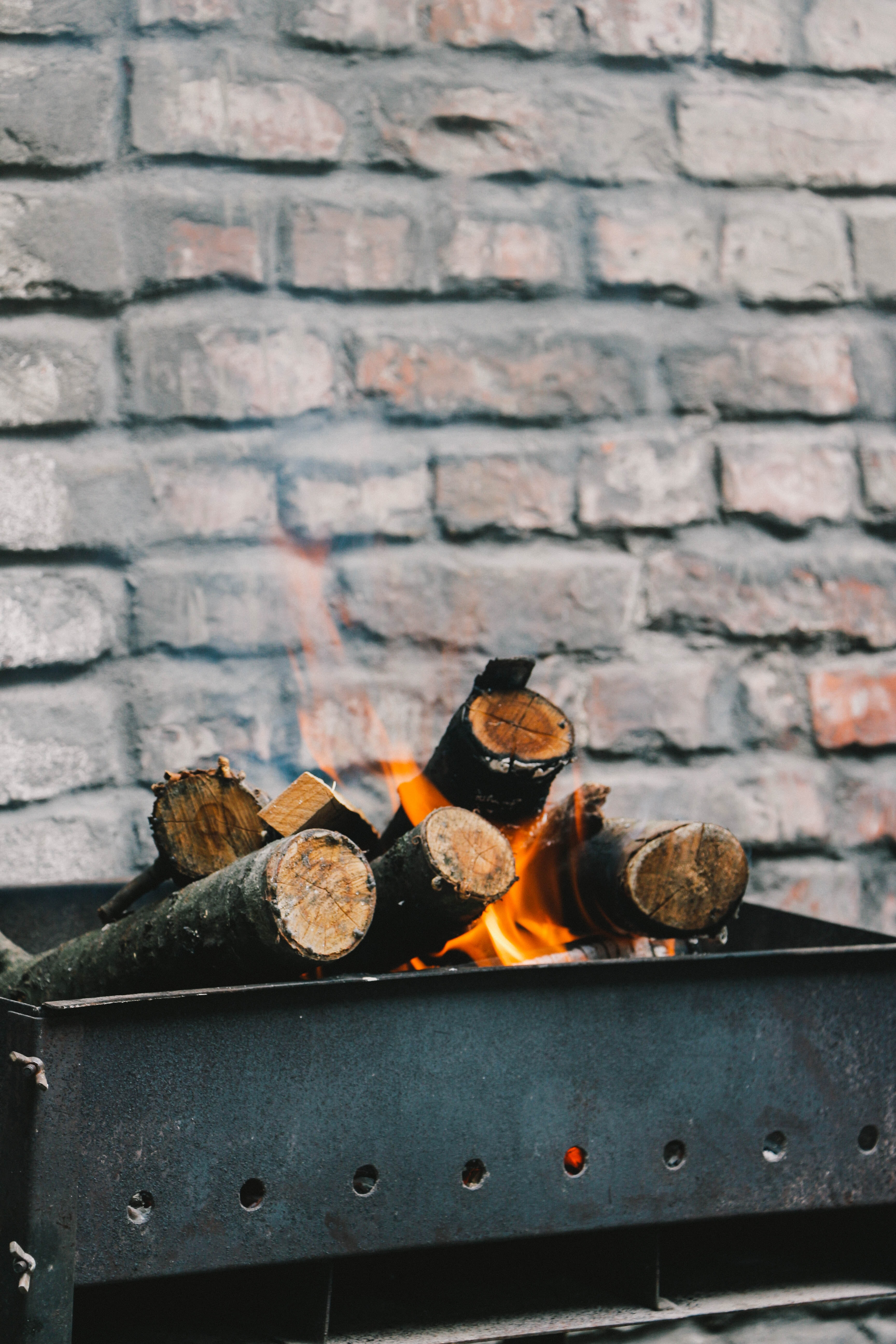 Burning firewood in a brazier next to a brick wall