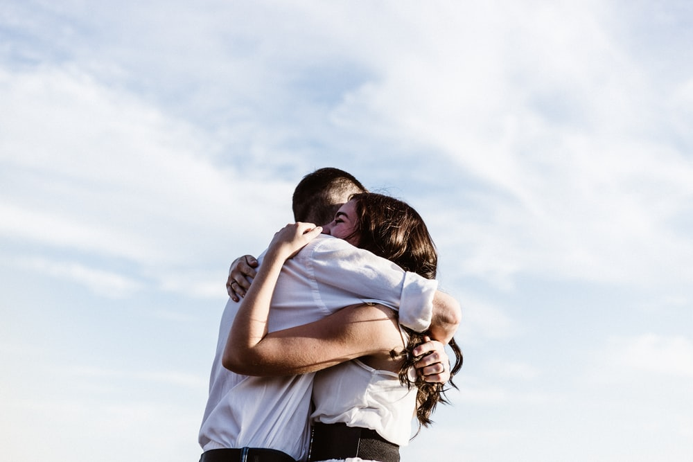 man and woman hugging each other photography