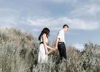 couple walks of grassy field