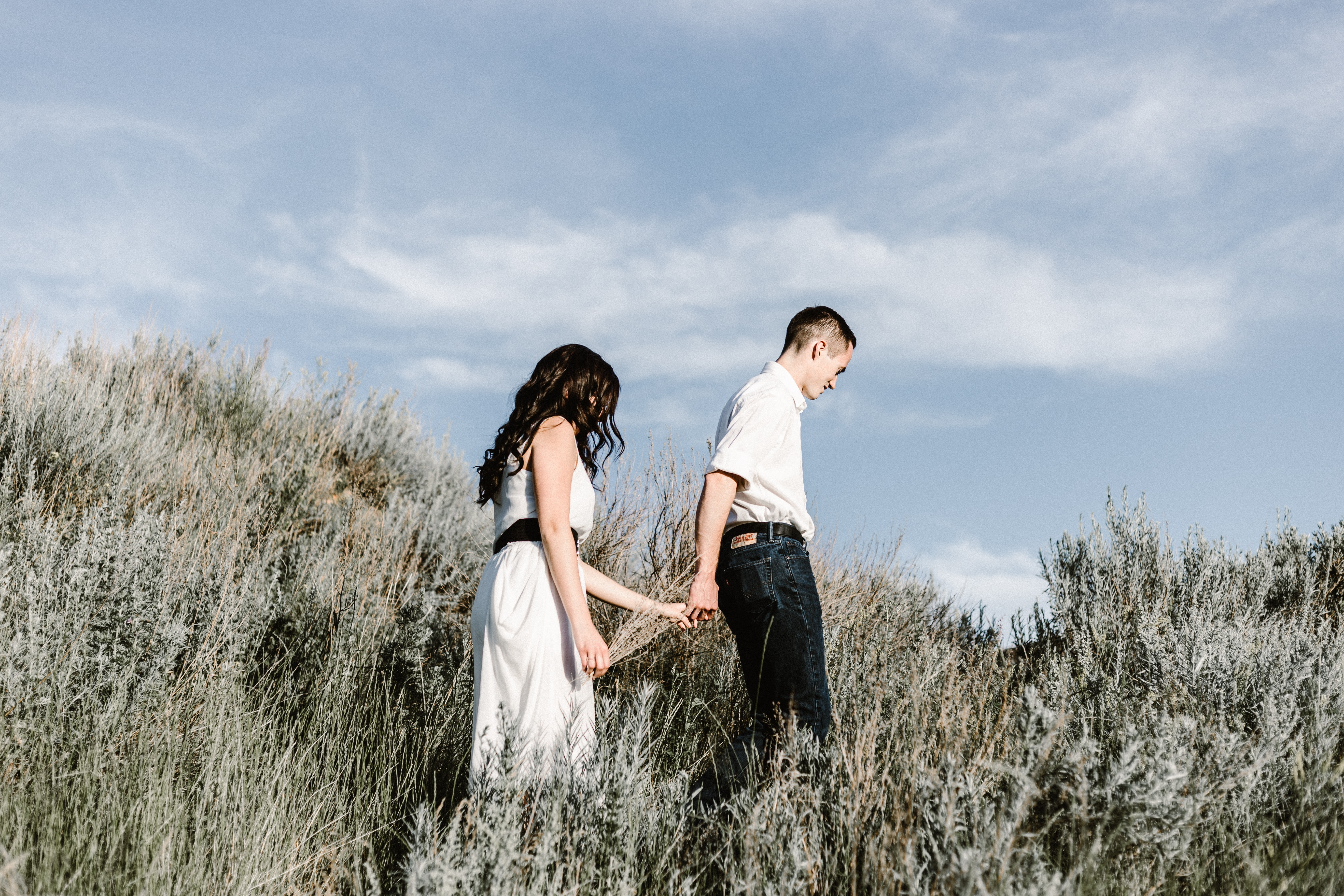 couple walks of grassy field