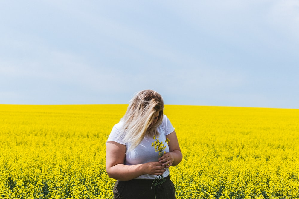 woman standing and holding flowers on flower field