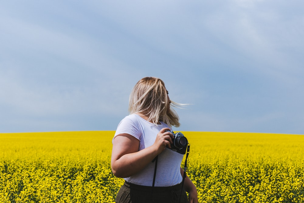 woman holding DSLR camera standing in front of yellow flower field