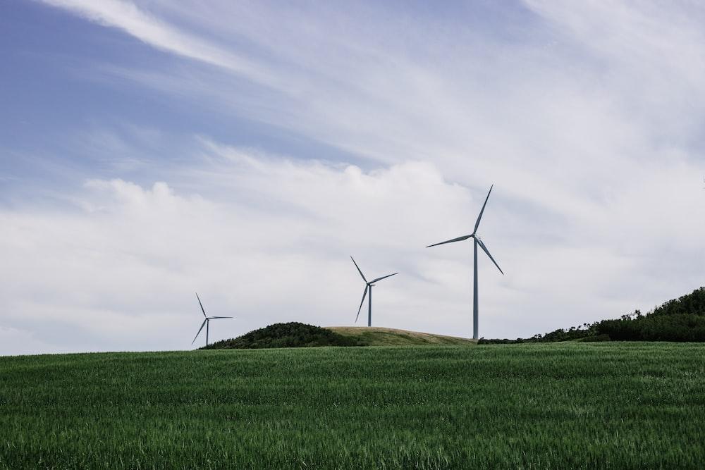 three windmill on green field