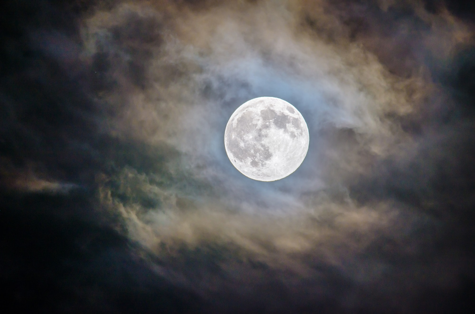 Clear image of a full moon in the night sky surrounded by fuzzy clouds.