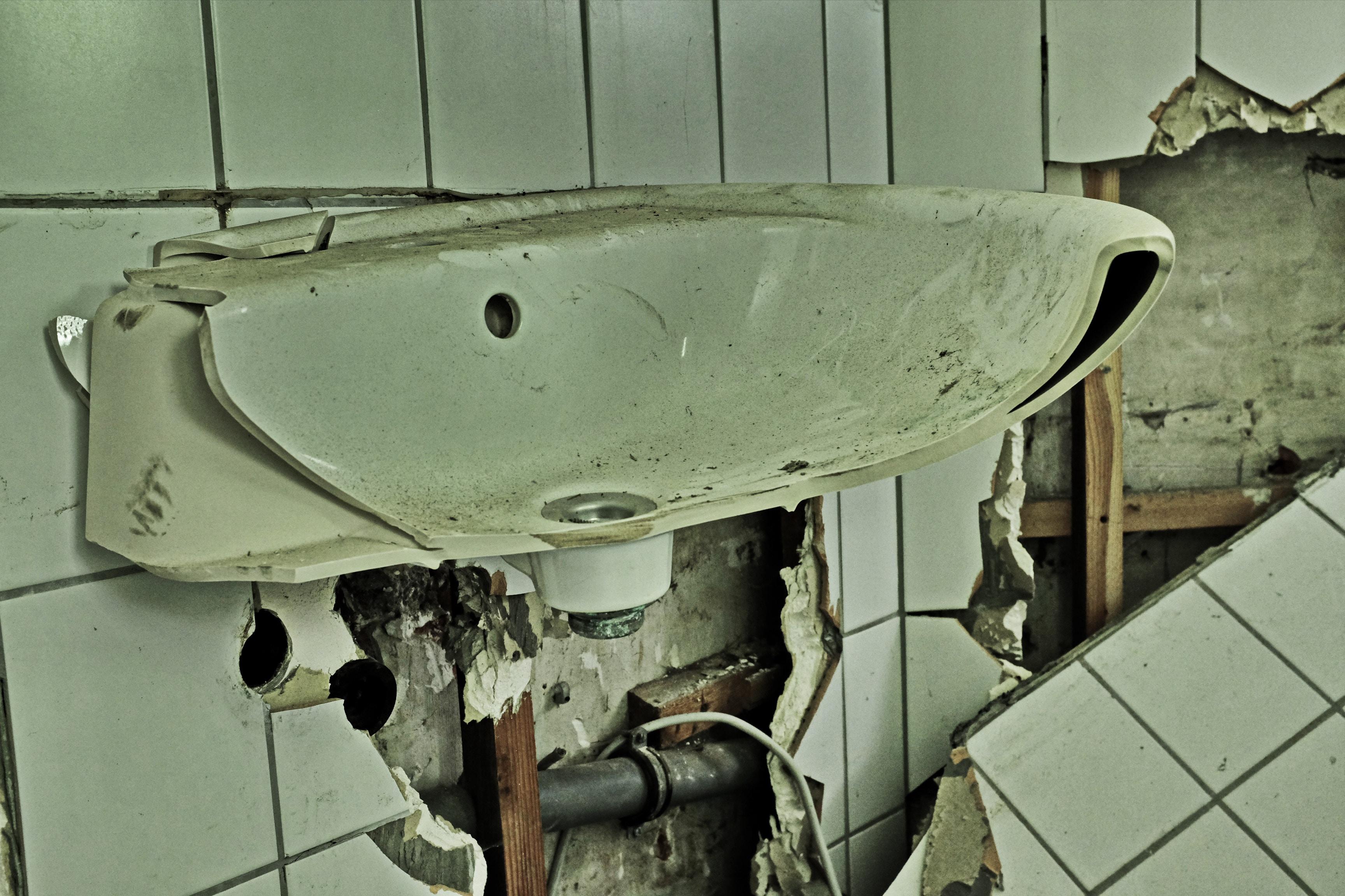 A broken apart bathroom sink vanity and wall.