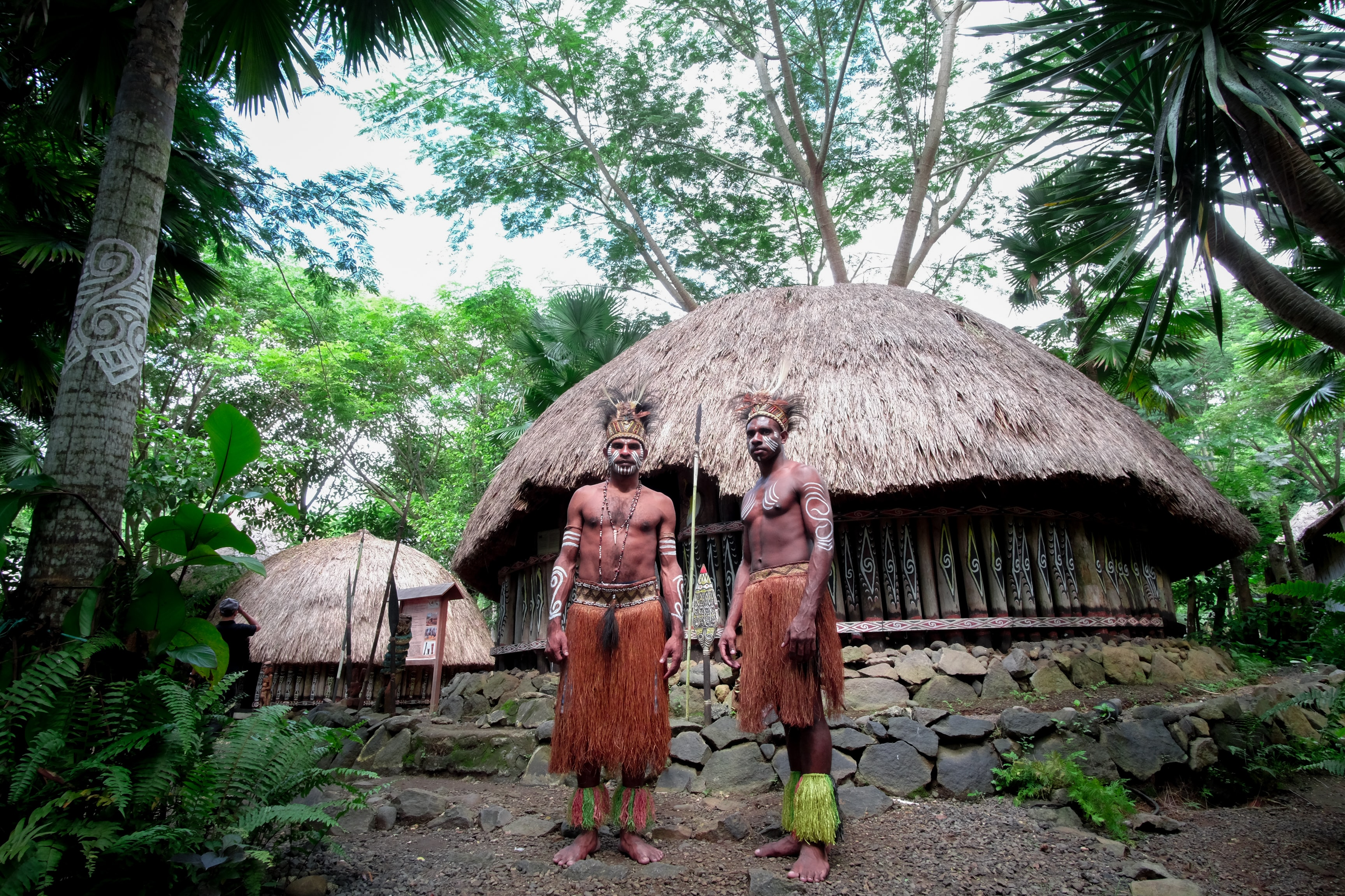 Two bare-chested men in tribal skirts and headgear near wooden huts in Bali