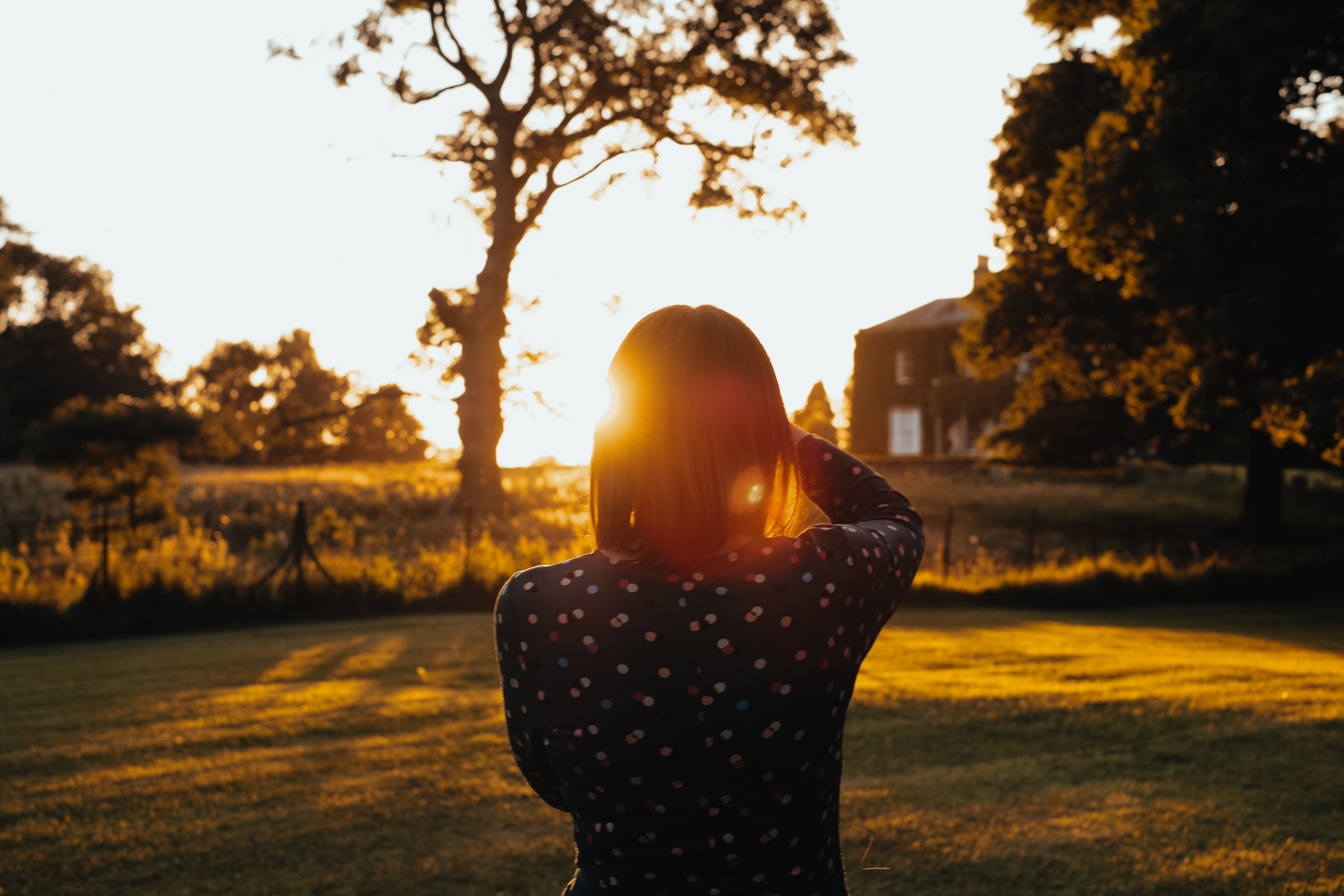 woman wearing black long-sleeved top standing on lawn during sunset