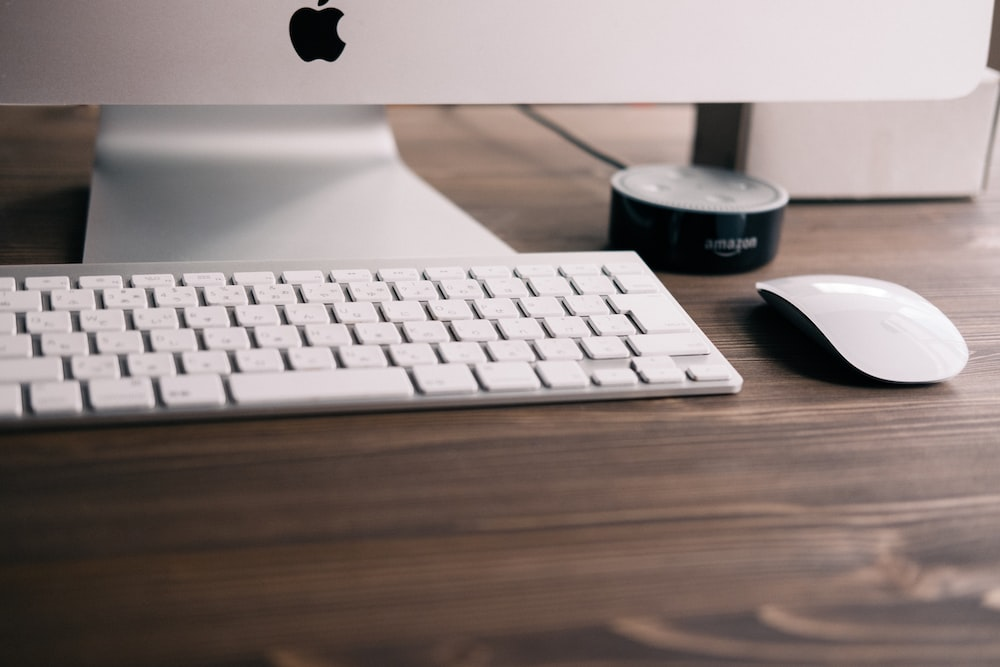 selective focus photography if silver iMac, Apple wireless keyboard, Magic Mouse, and black Amazon Echo Dot 2nd generation at table
