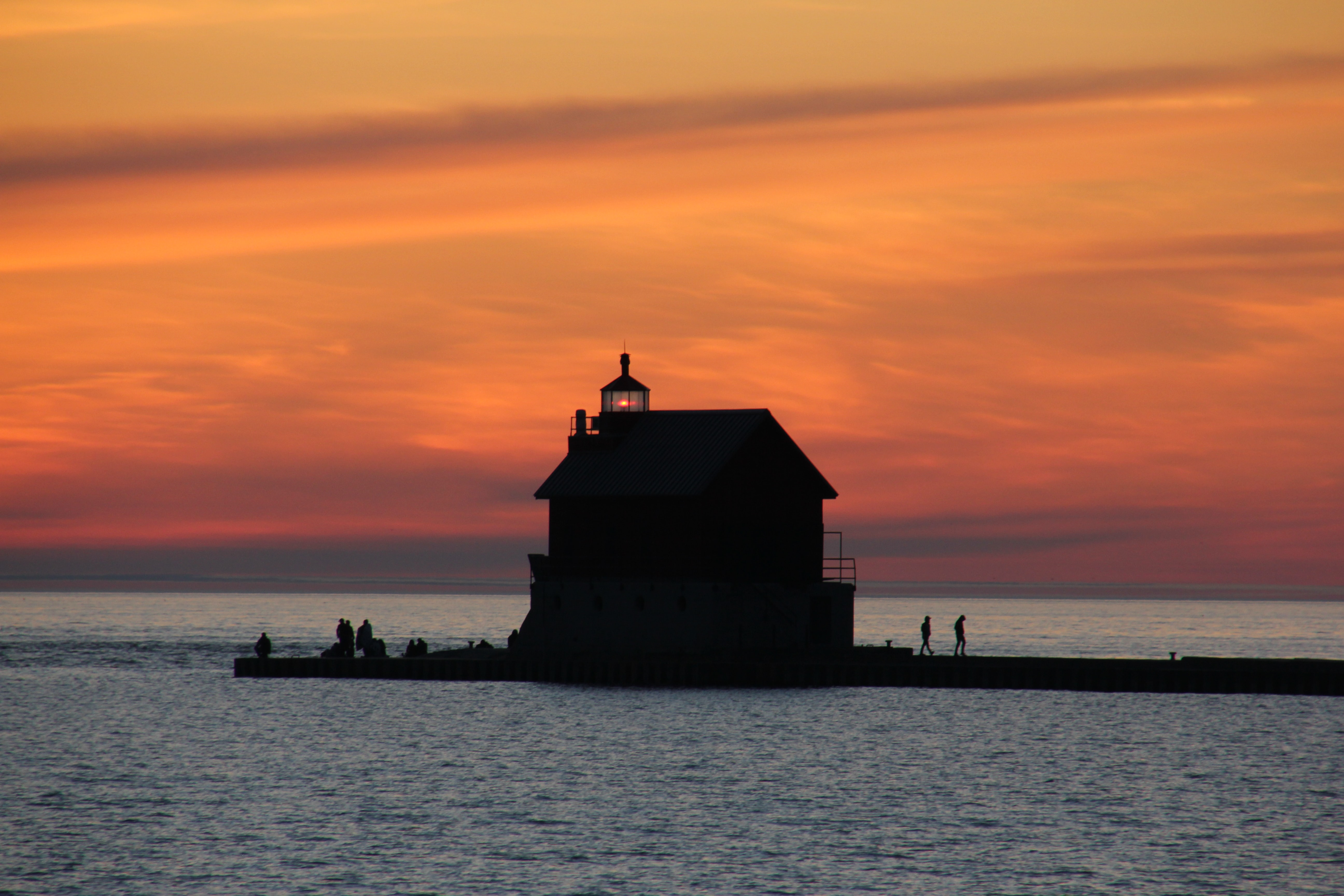 Distant shot of a small lighthouse in the sea, with people around, a cloudy orange sunset above