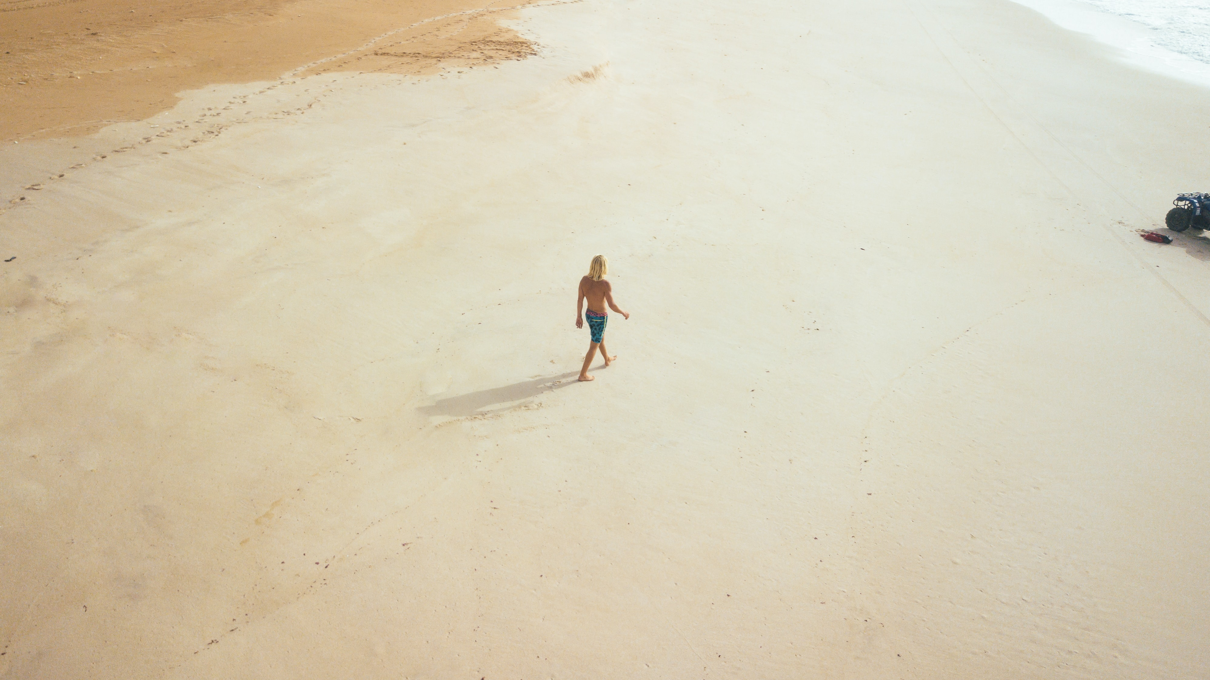 A high-angle shot of a person walking along an empty beach on a sunny day