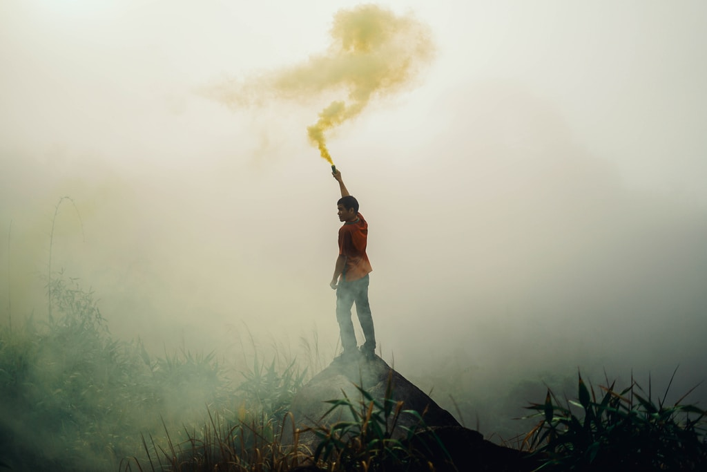 man standing on rock formation holding yellow flare surrounded by fogs