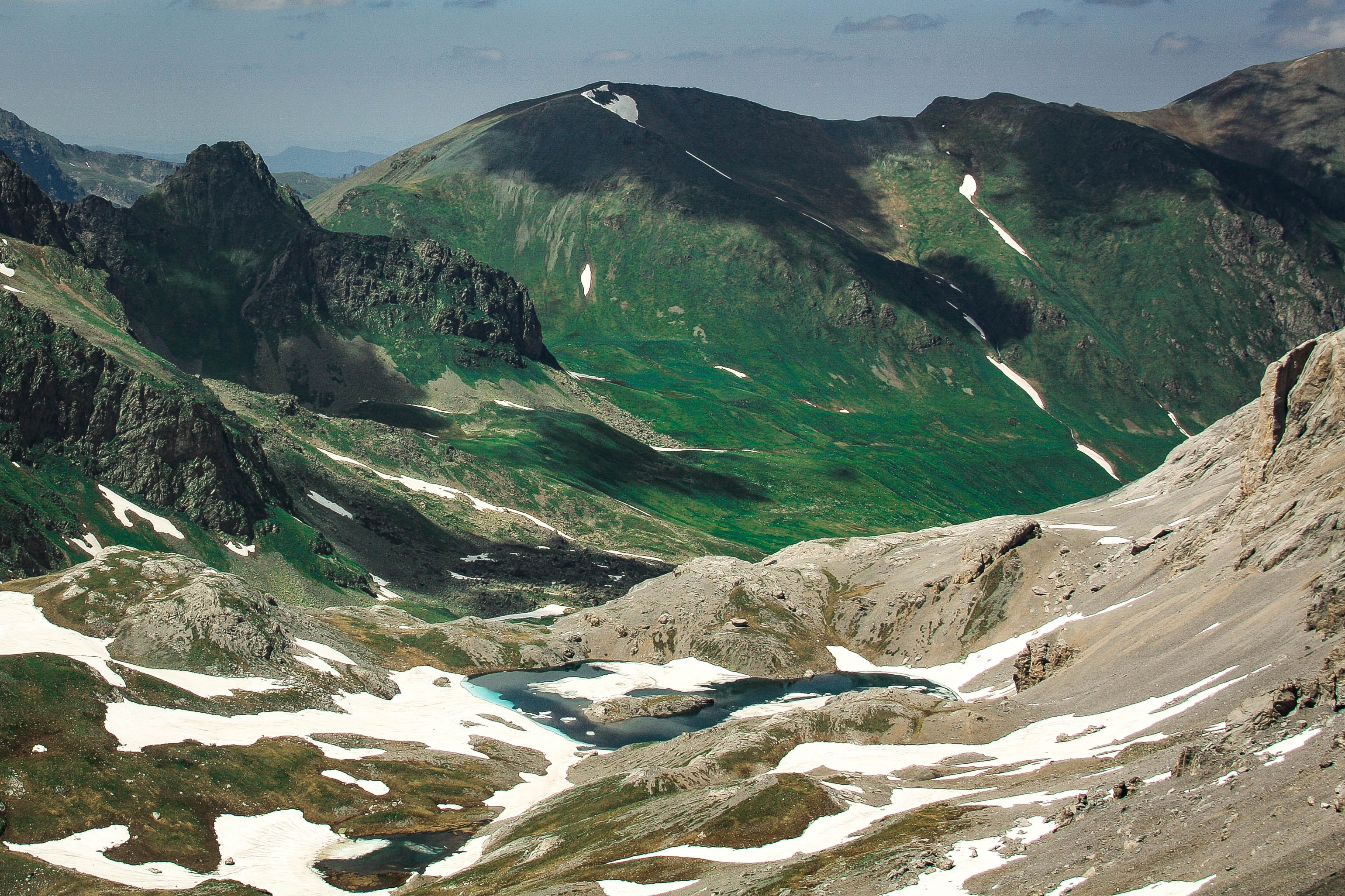 A mountain valley with small pools of water and patches of snow in Arkhyz