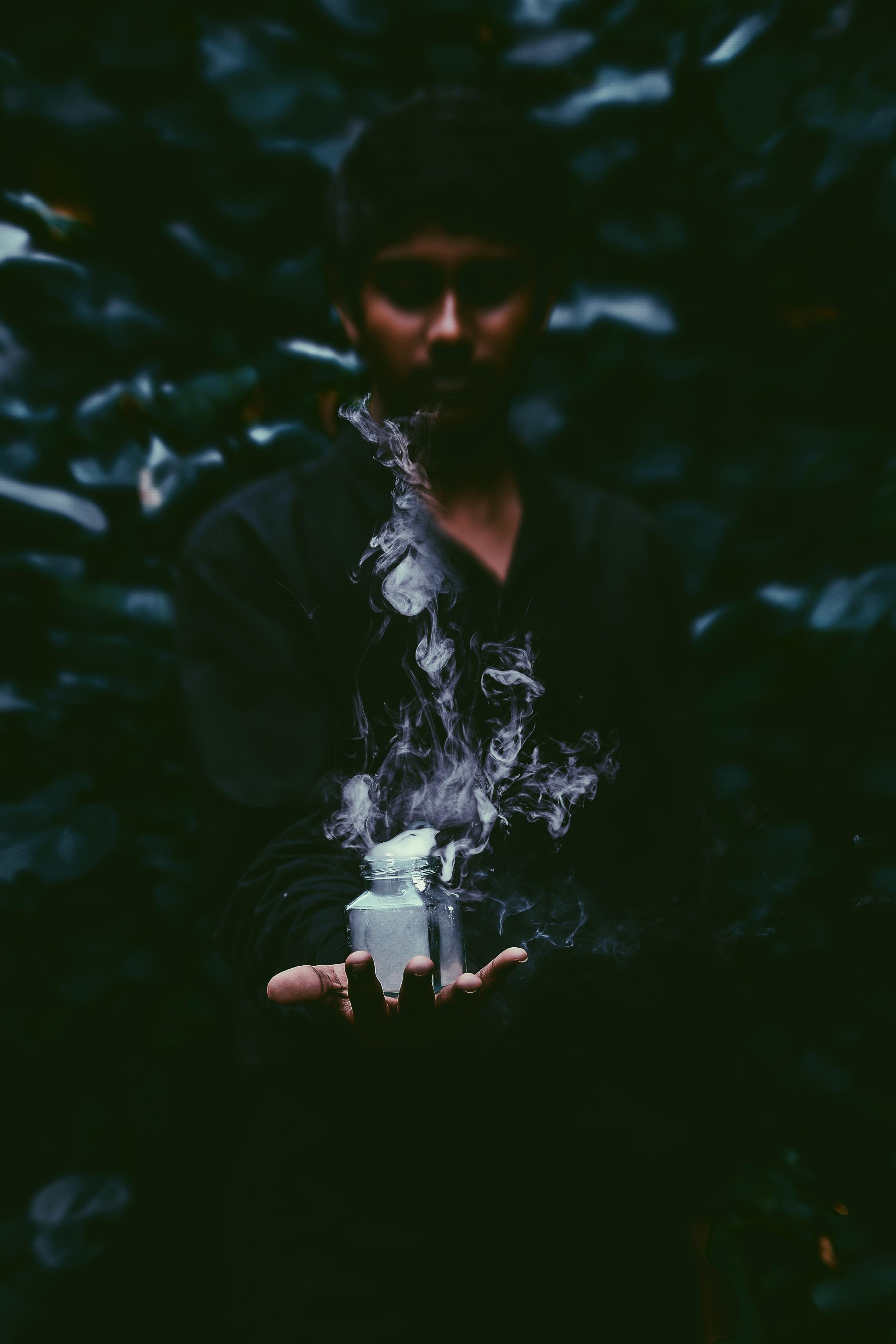 man holding jar with smoke