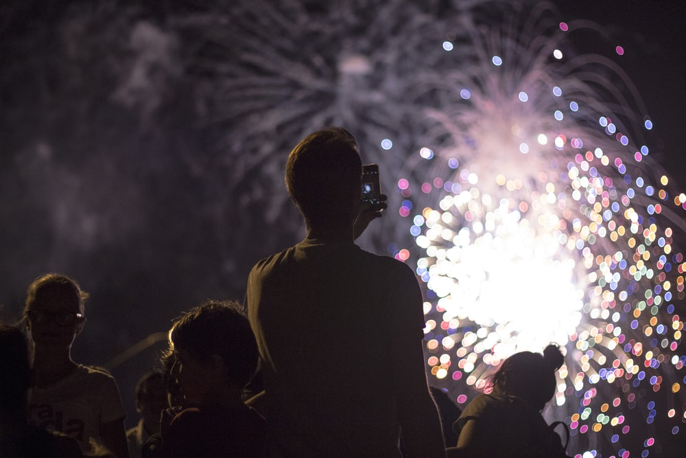 man taking picture of firecracker