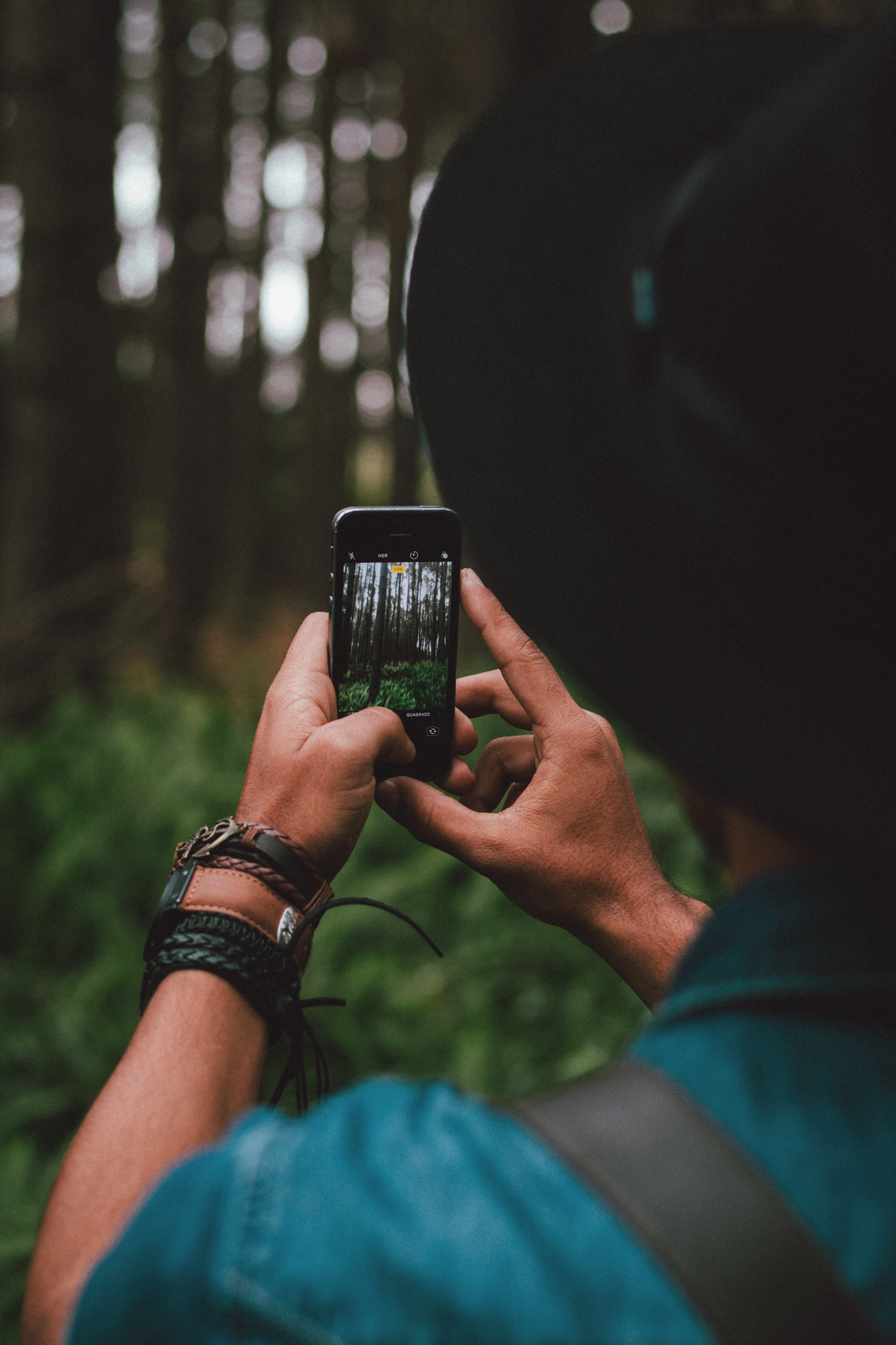 A man is taking a photo of a forest with his iPhone in Cianorte.