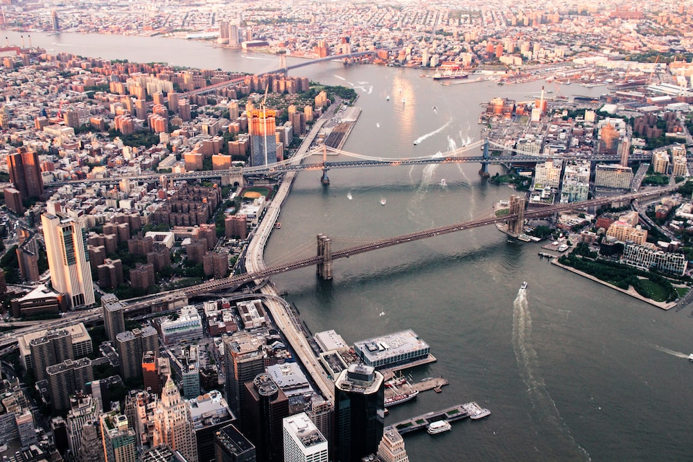 body of water between island with building and bridge at daytime