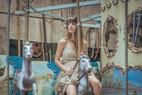 woman in gray floral dress riding carousel