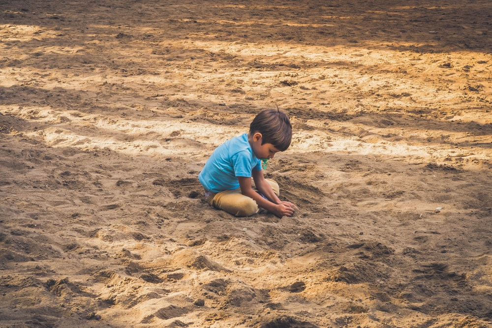 boy playing on sand during daytime
