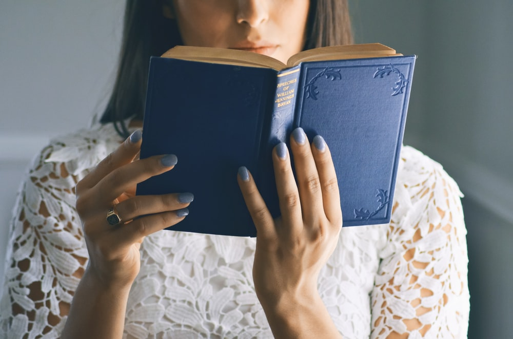woman wearing white floral top reading bible