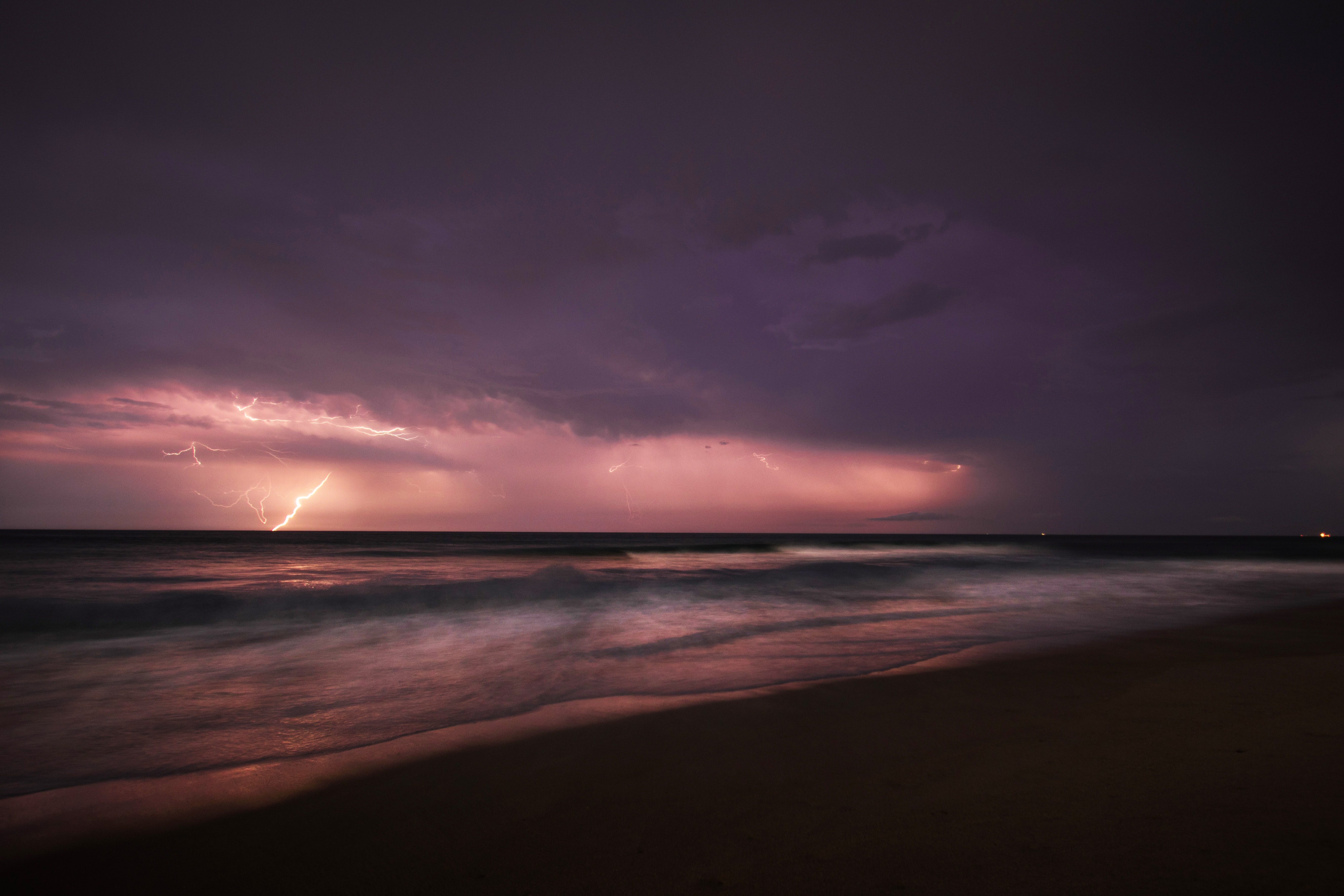 A bolt of lightning erupts from the clouds during a purple sunset over the Southern Shores