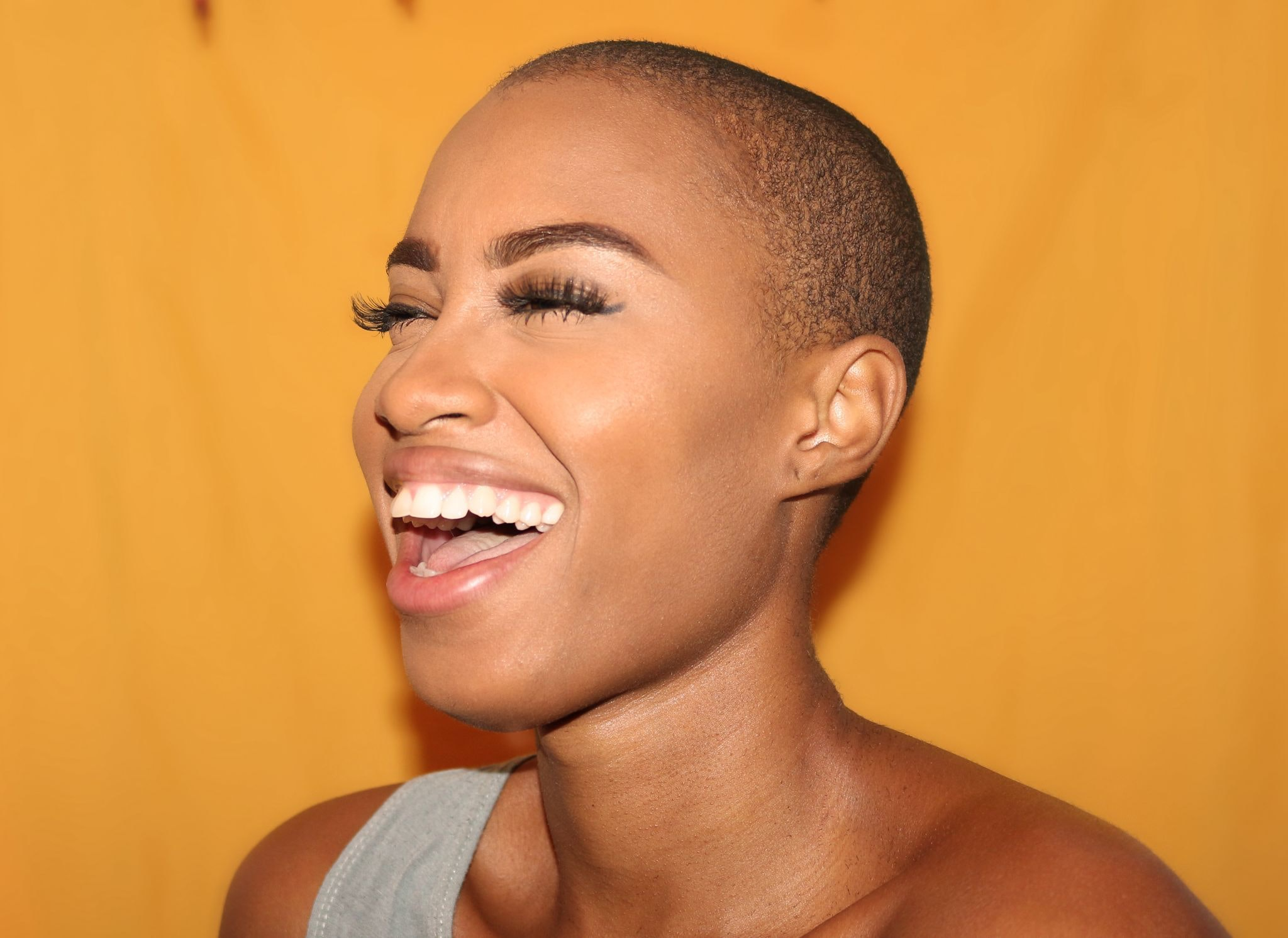 A woman with a shaved head smiles broadly against a yellow background