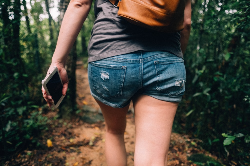 woman holding phone walking toward trees