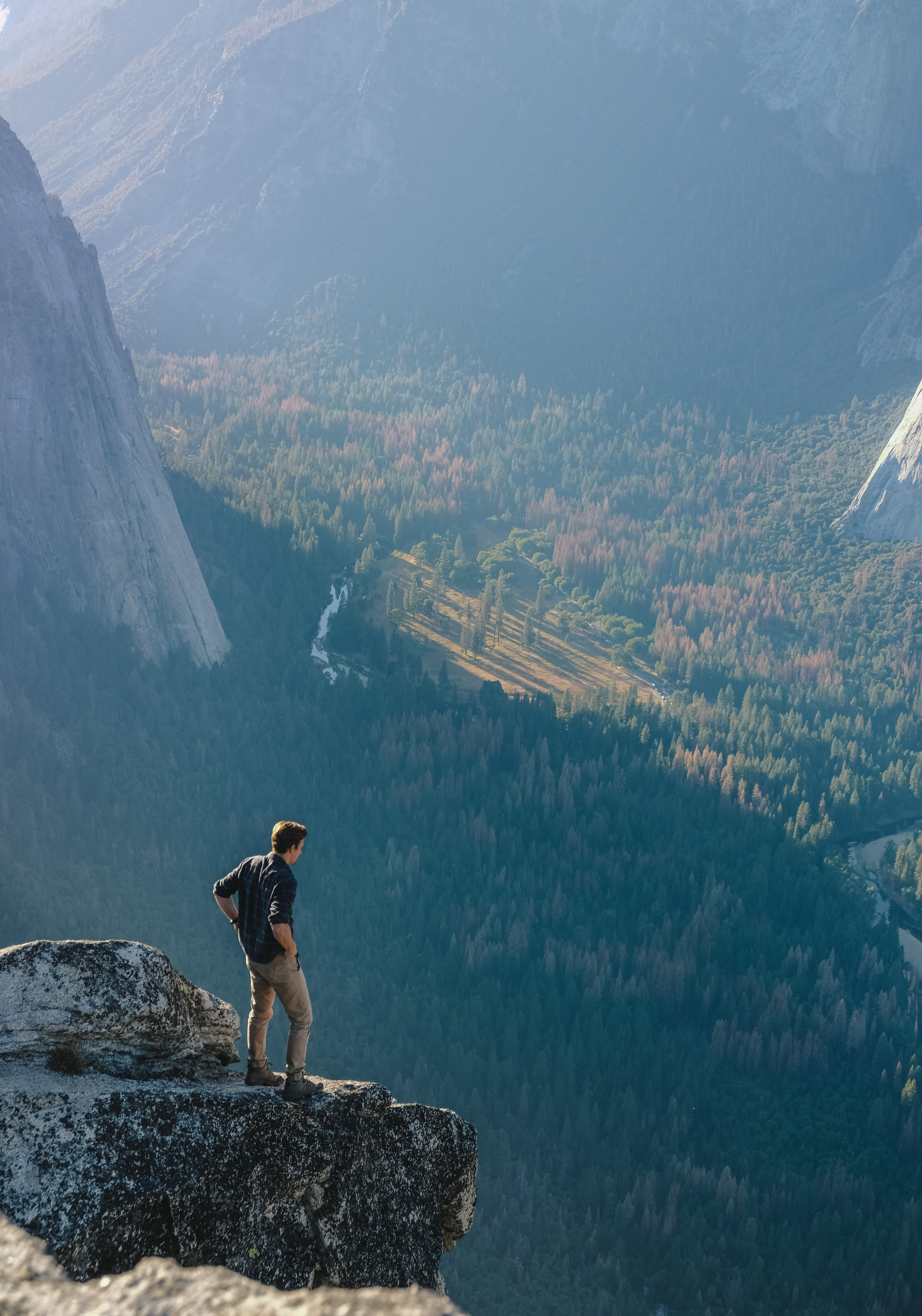A man standing on a ledge with a view on the floor of Yosemite Valley