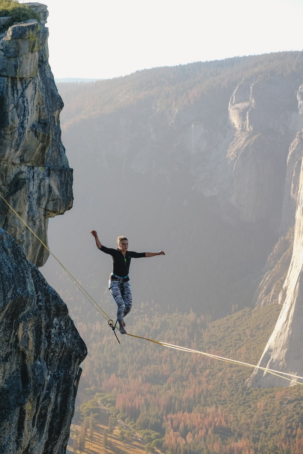A woman walking on a tightrope high up in the Yosemite Valley