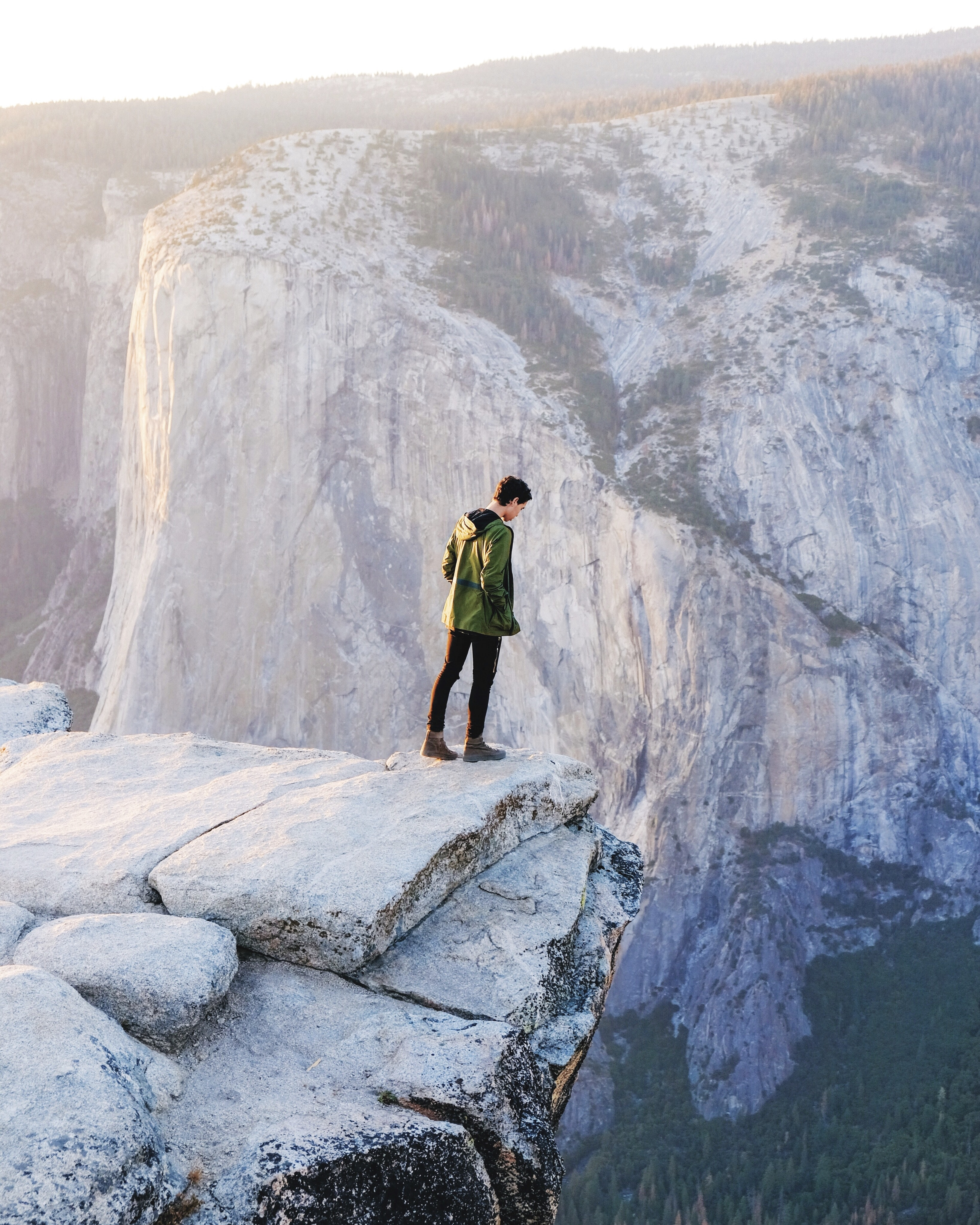 A man wearing black pants and a green jacket leaning over the edge of a cliff in Yosemite Valley