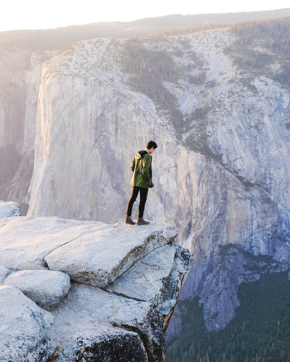 standing man looking on cliff at daytime