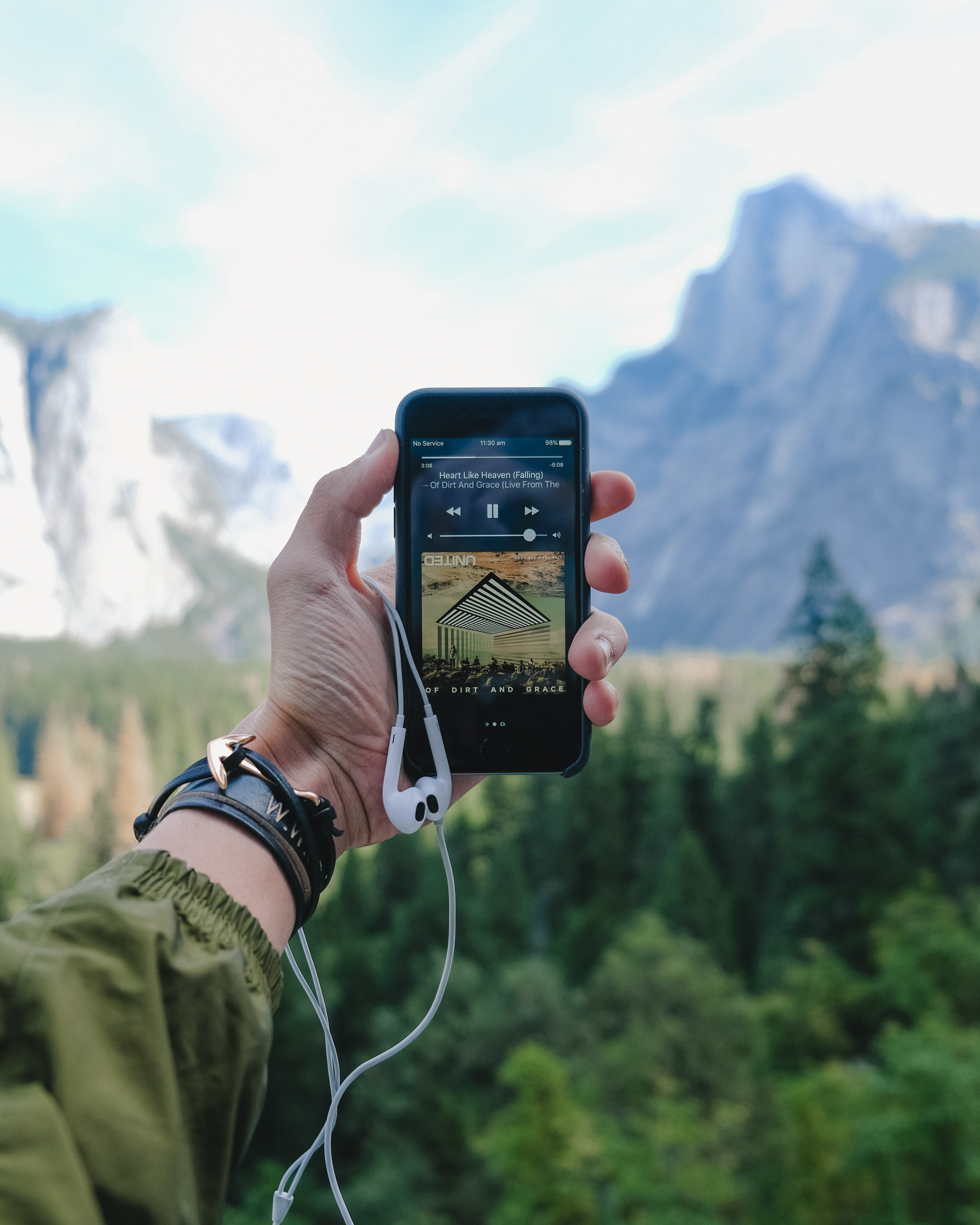 A person's outstretched hand holding an iPhone with a music player in the Yosemite Valley