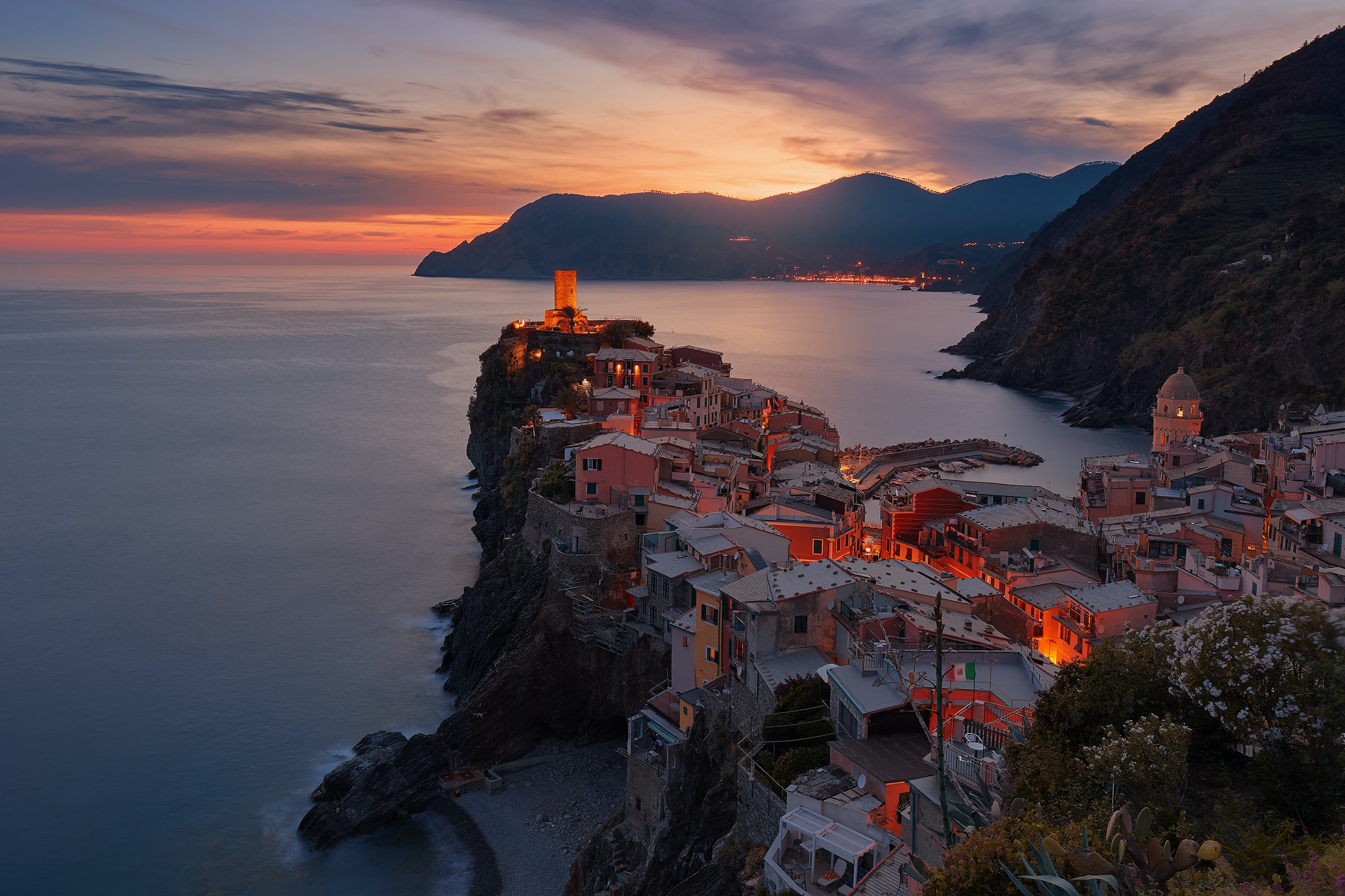 Coastal town of Vernazza in Italy, its buildings glowing orange as the sun sets behind a mountain