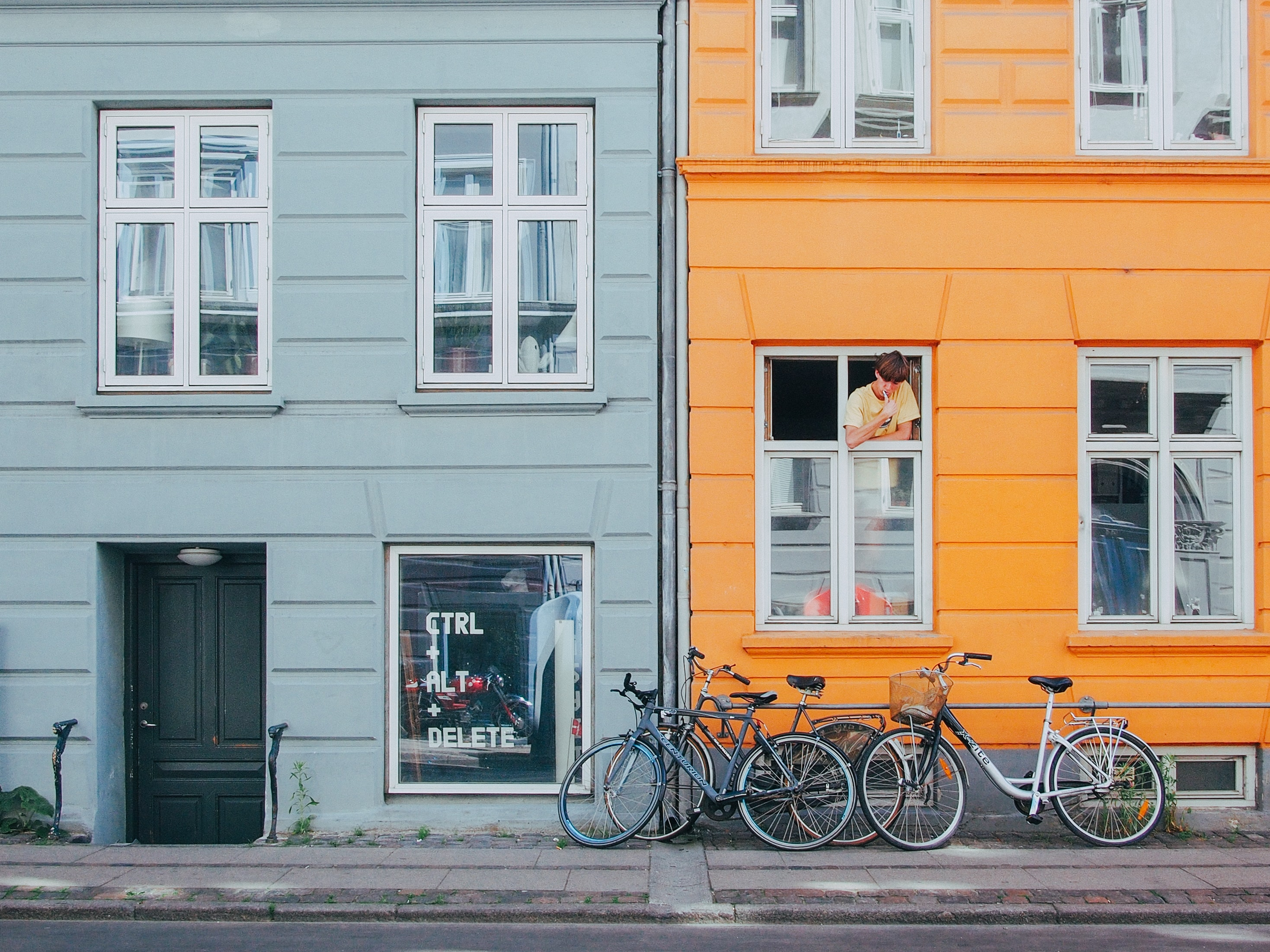 person on window looking at bicycles during daytime
