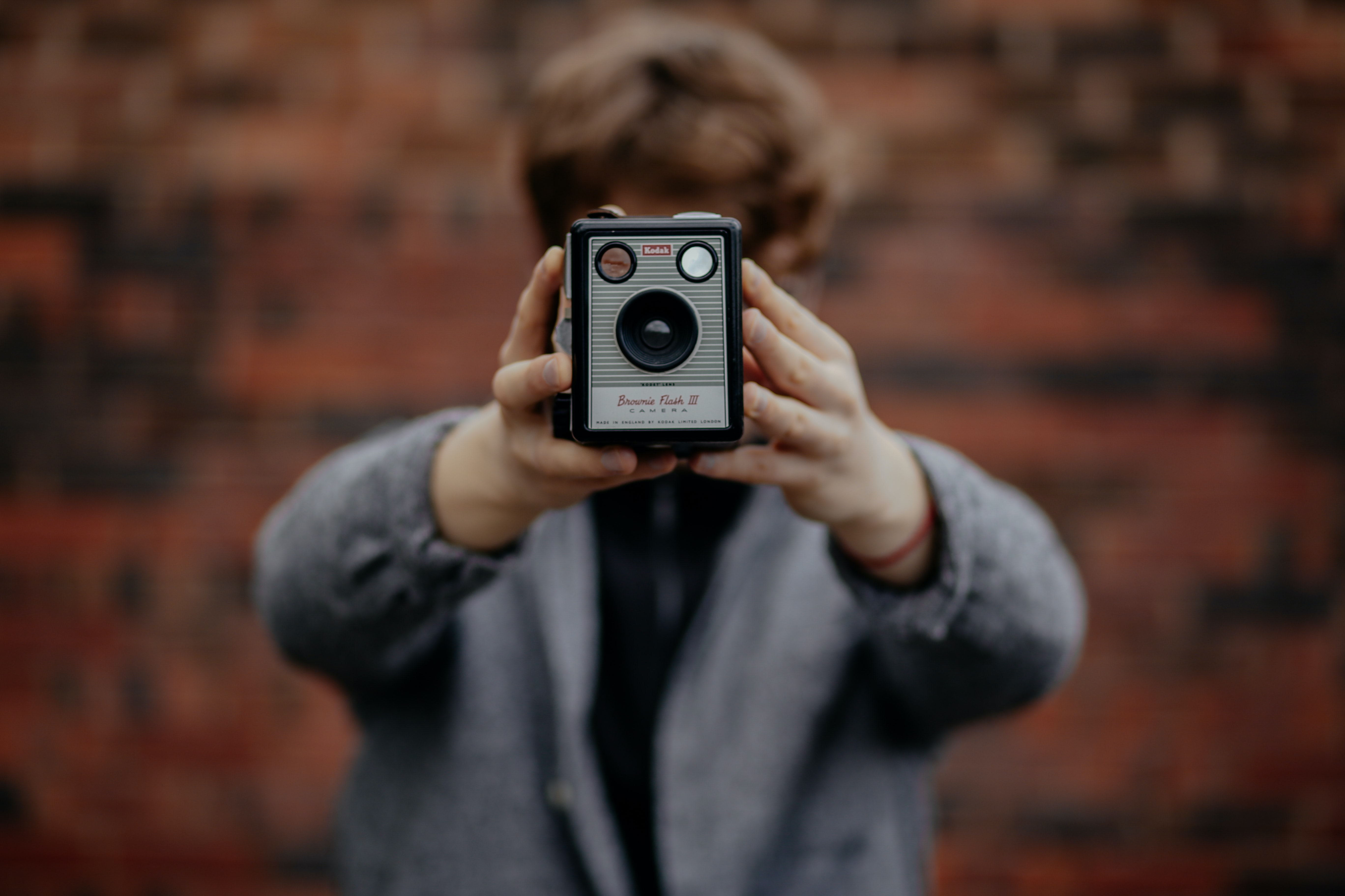 A person with short brown hair and a gray sweater taking a selfie with a vintage Kodak camera covering his face