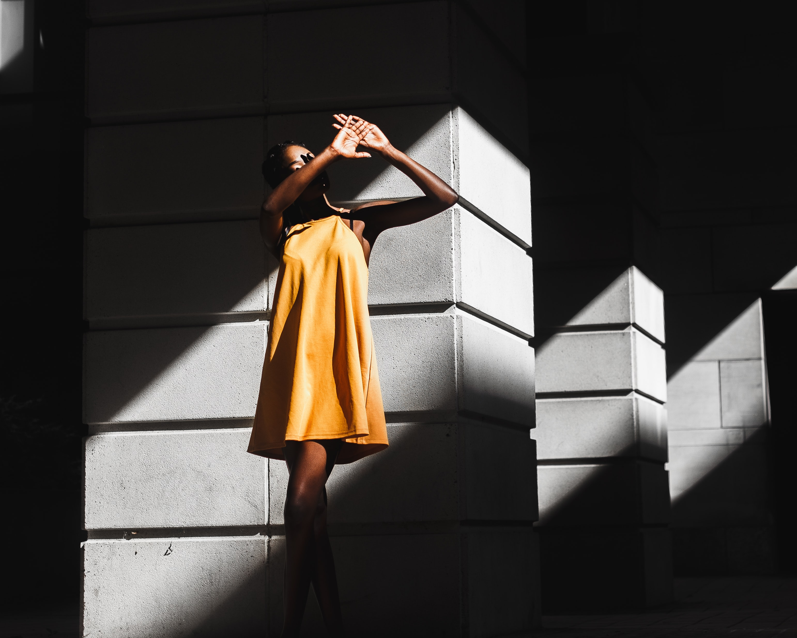 Woman in a yellow dresses blocks sunlight from her face while standing in the shadows