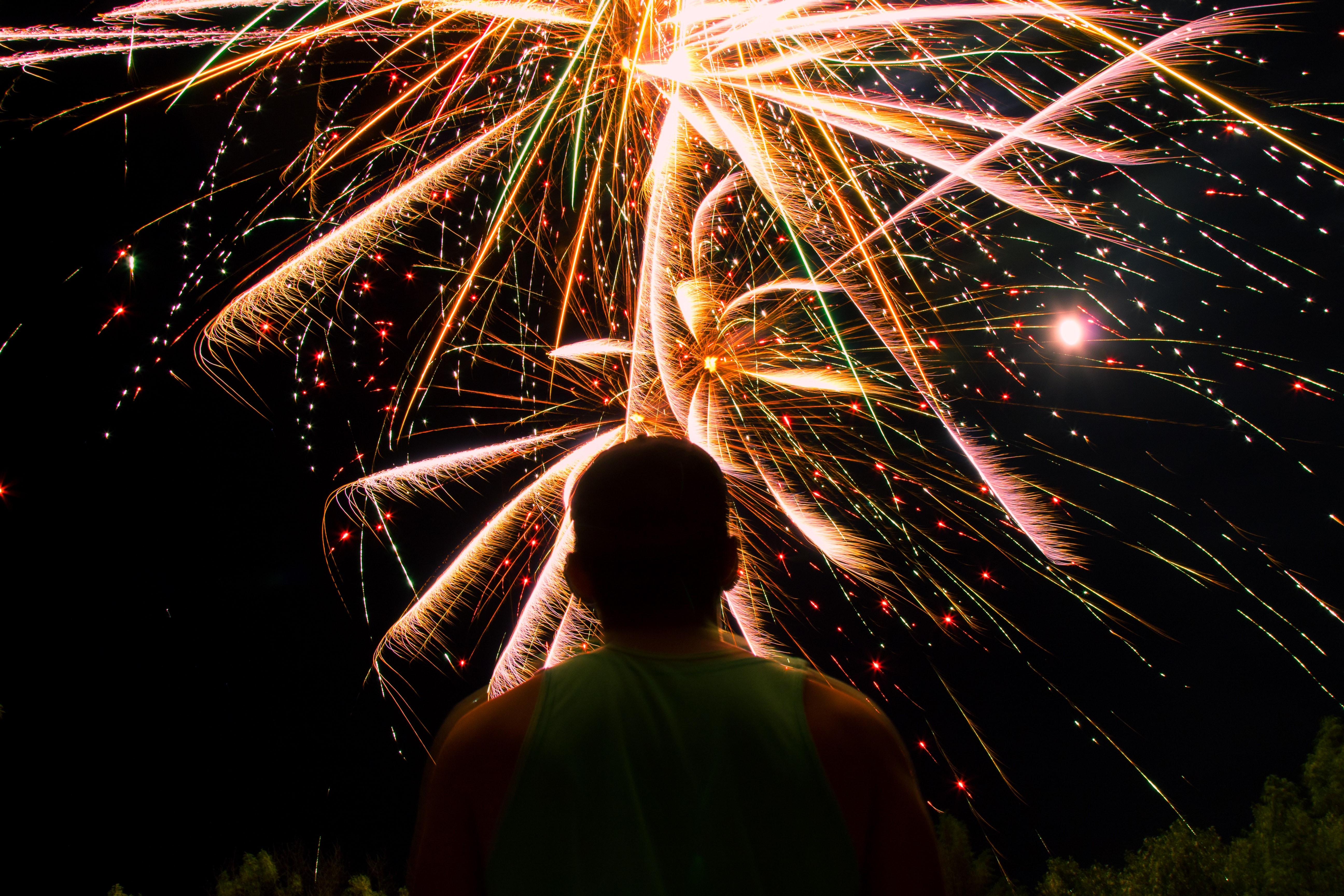 man watching over firework display during nighttime