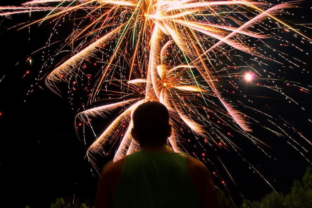 man watching over firework display during nighttime