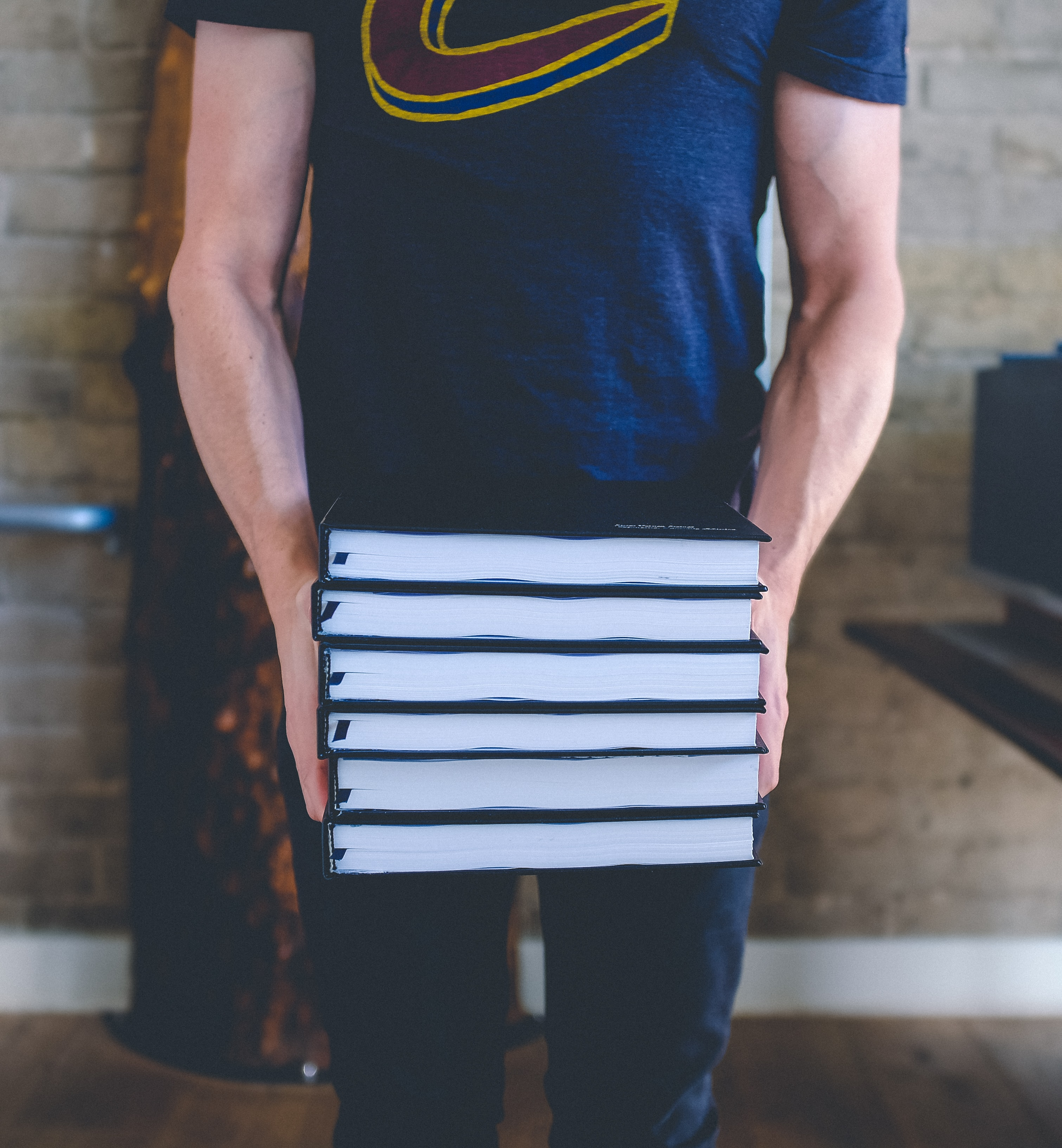 Person in a t-shirt carries a stack of books in front of an indoor brick wall