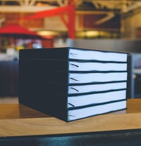 six black books on top of brown wooden table