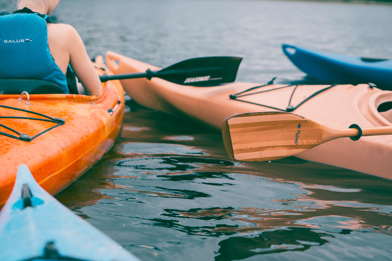 person riding on orange kayak during daytime