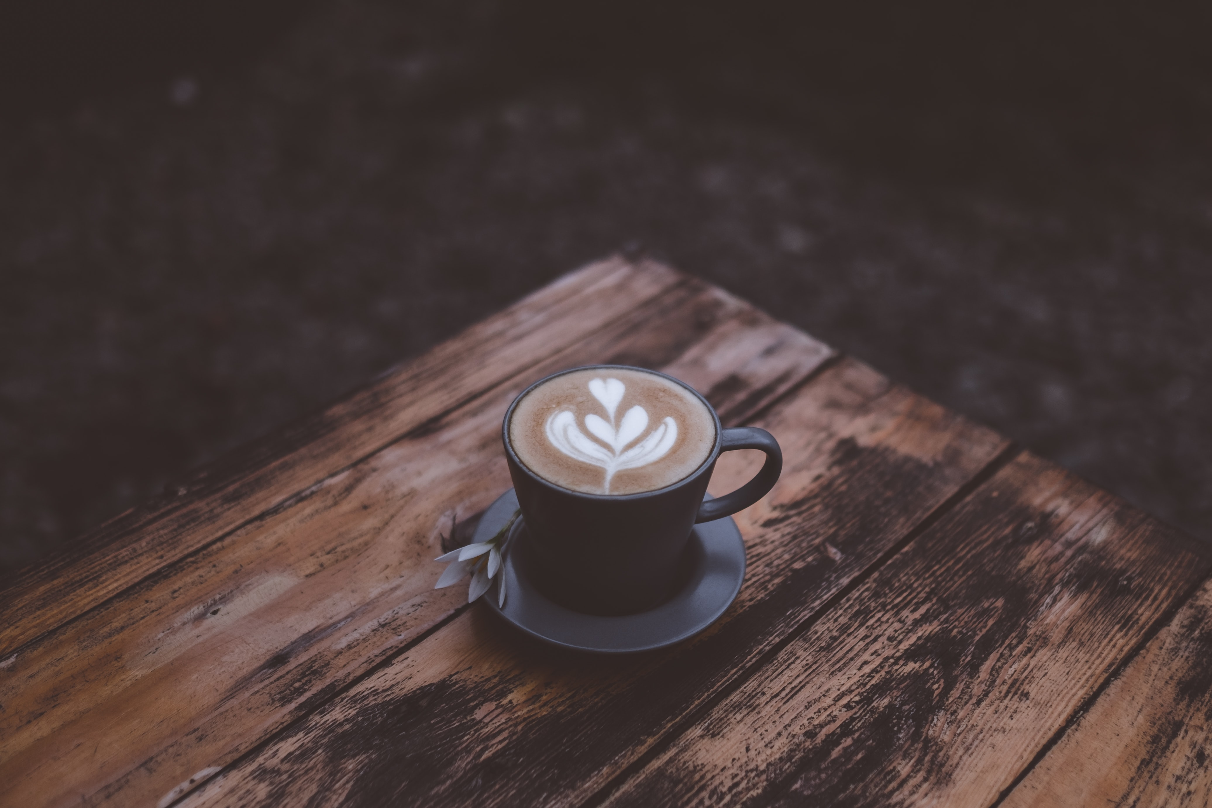 Latte art on textured wooden table in black cup