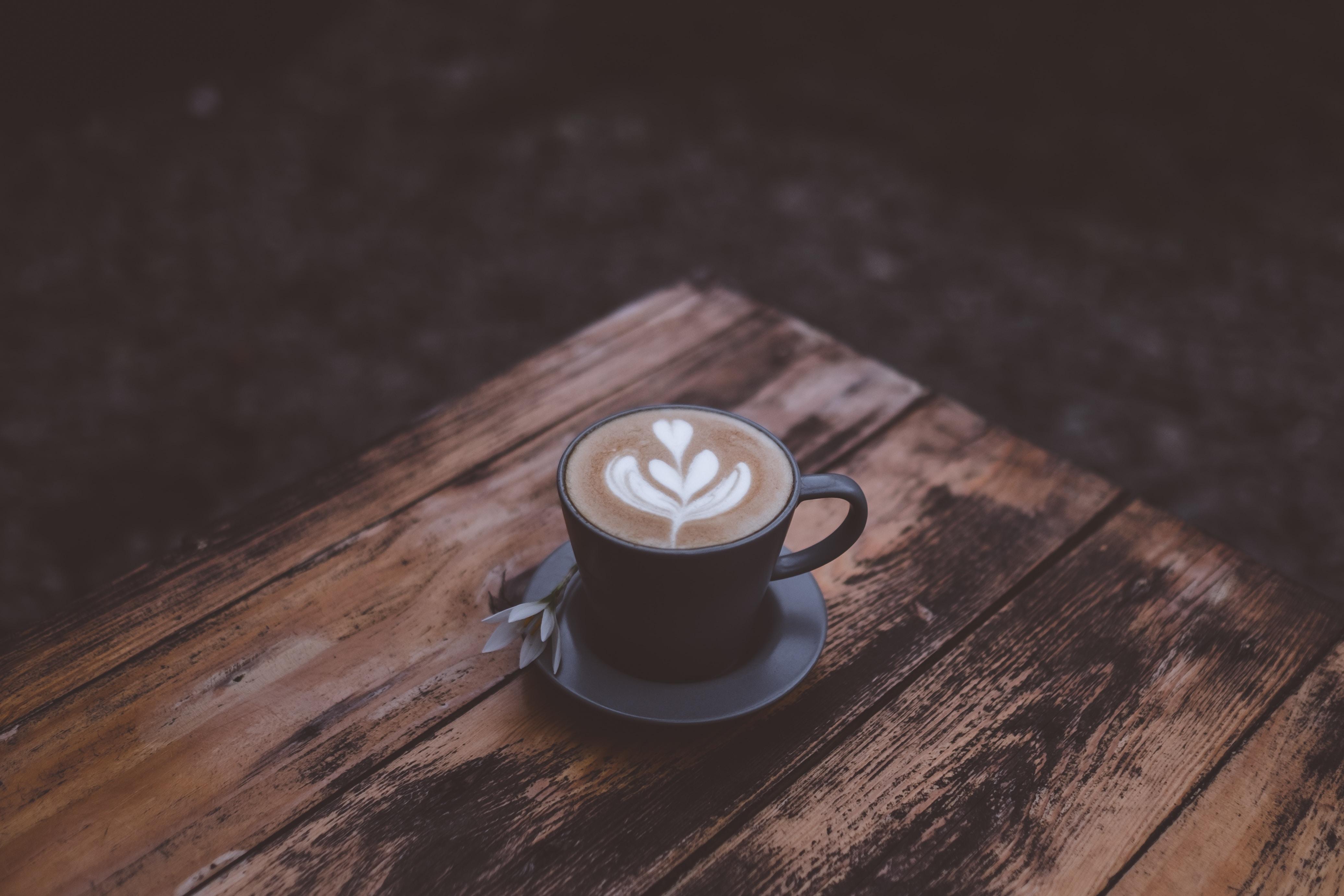 black ceramic mug with latte on table