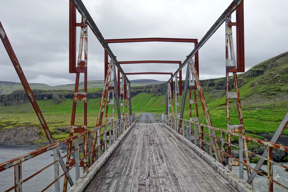 red metal bridge over green grass field during daytime