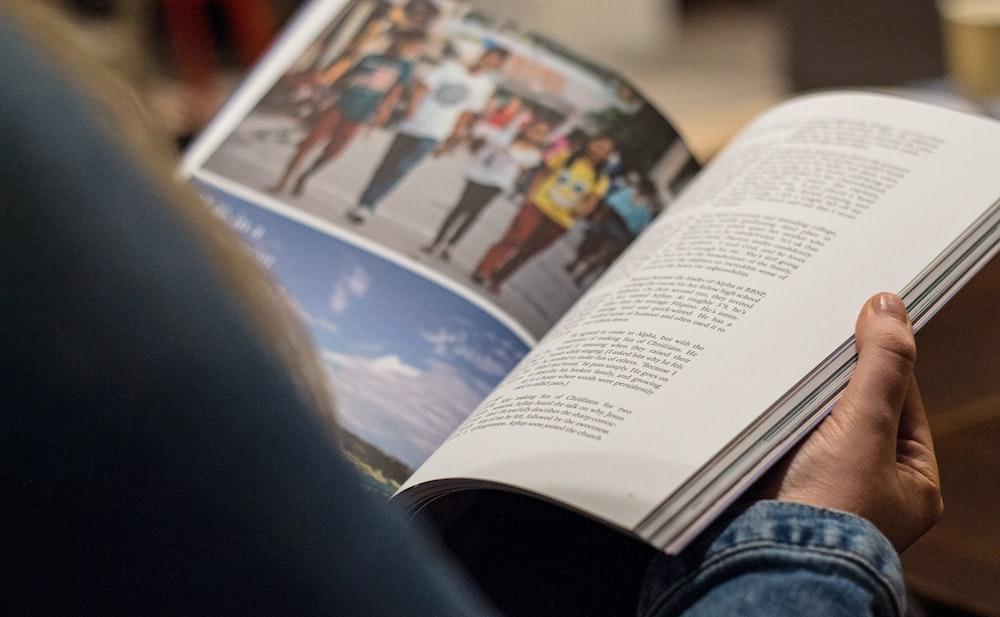 person in blue denim top reading book