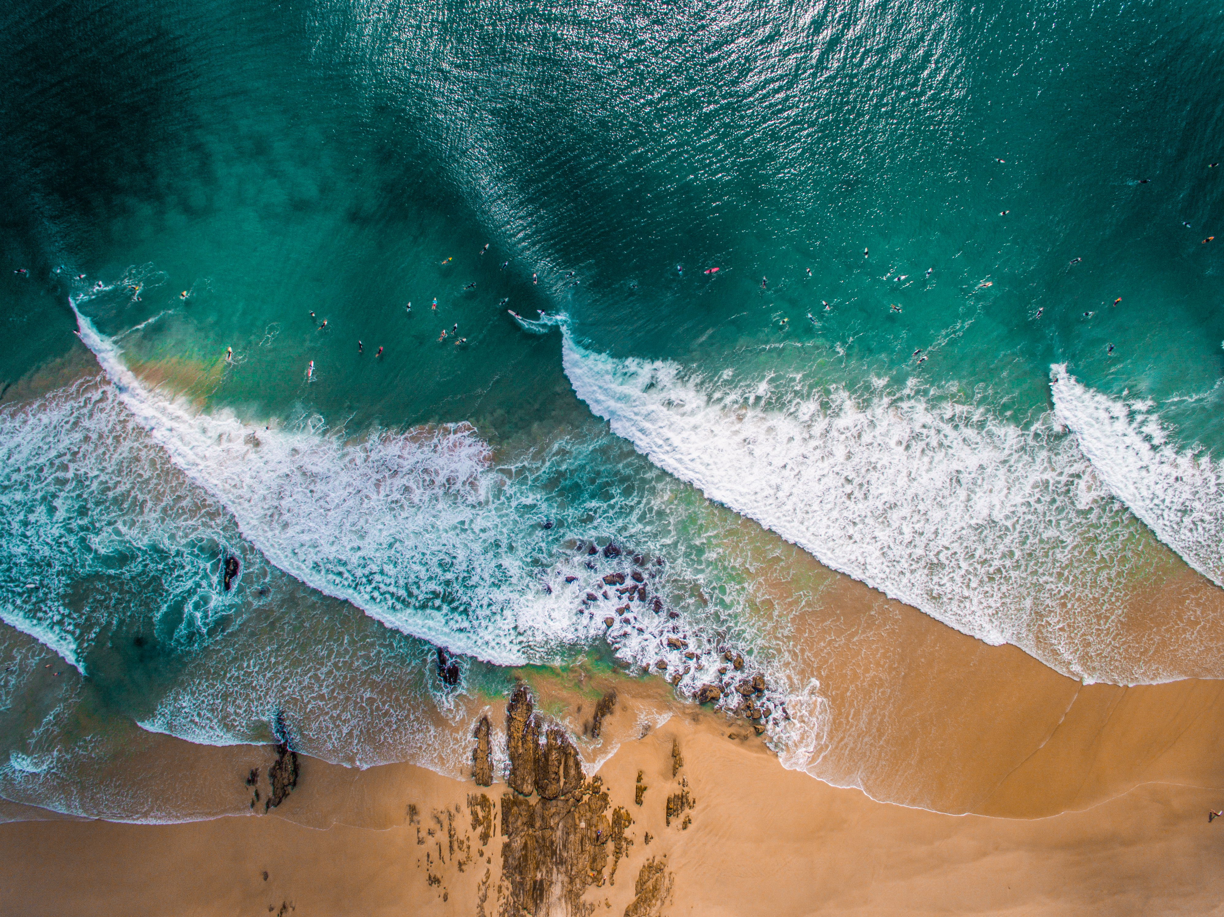 Drone aerial view of the waves crashing on the sand beach at Snapper Rocks Road