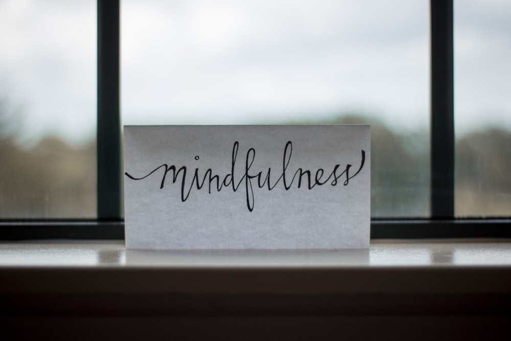 "A piece of paper with ""mindfulness"" written in cursive"