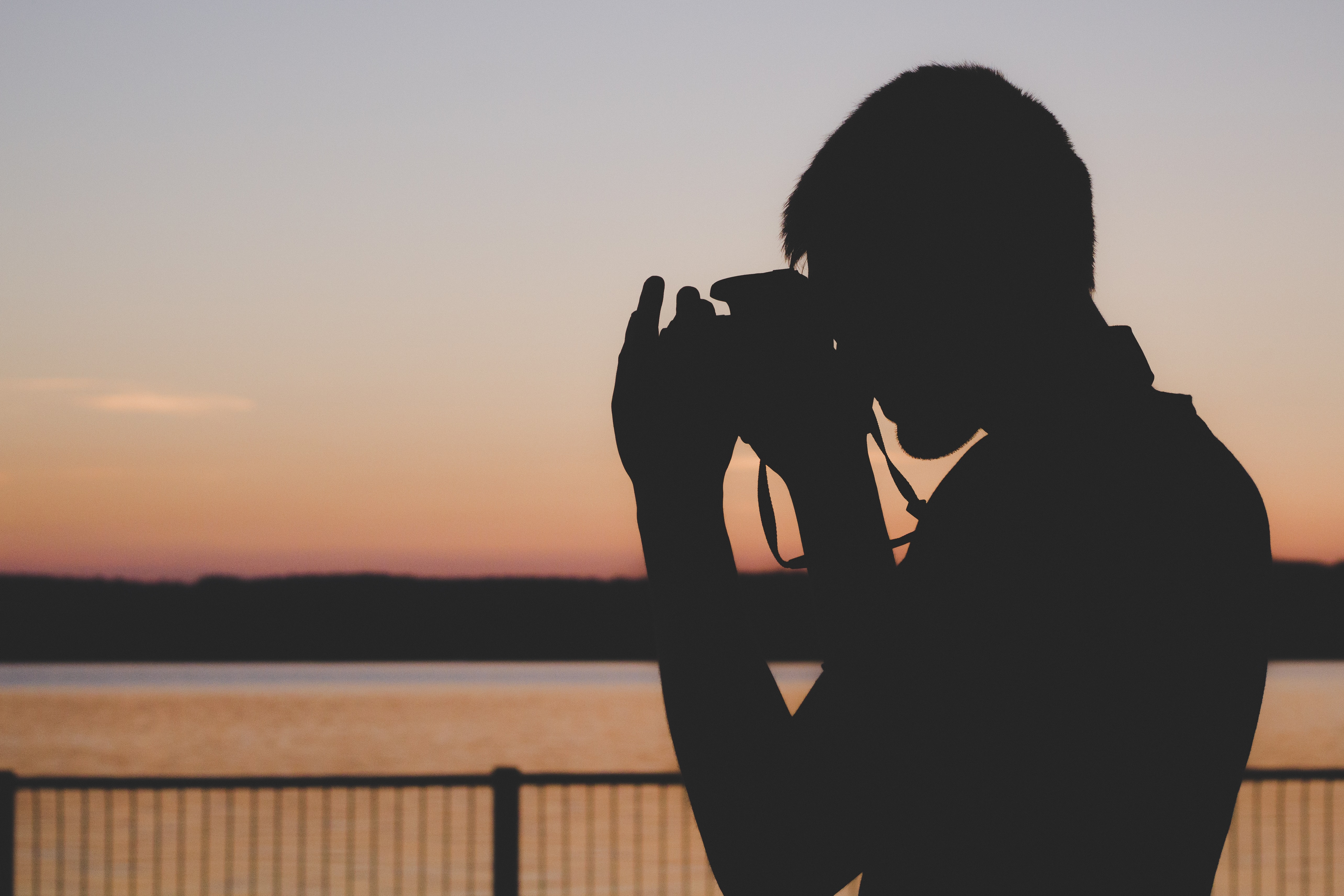 silhouette of man using camera near balustrade during sunset