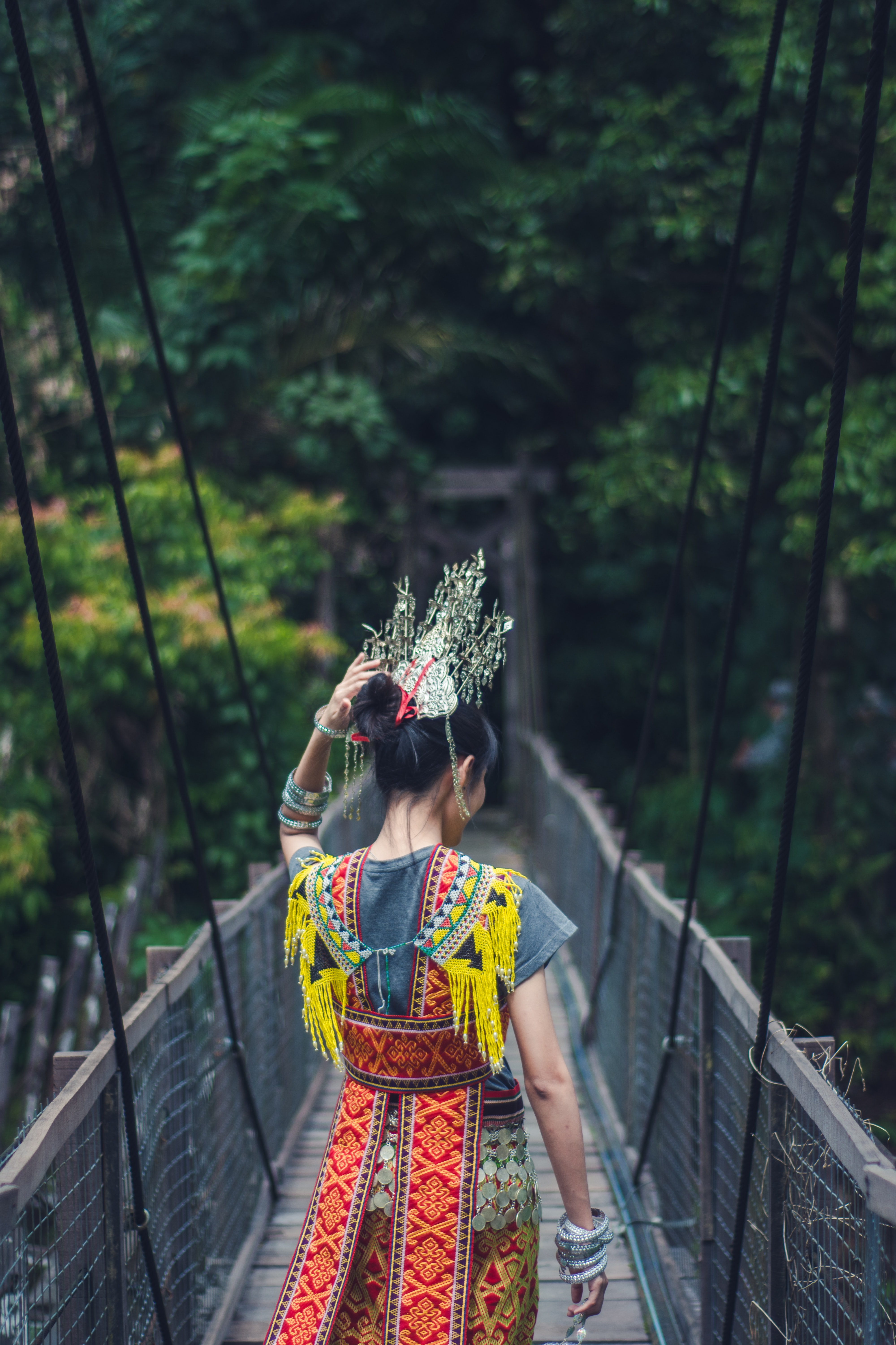 A person in a headdress and brightly-colored costume walks on a suspension bridge in Ulu Bayor